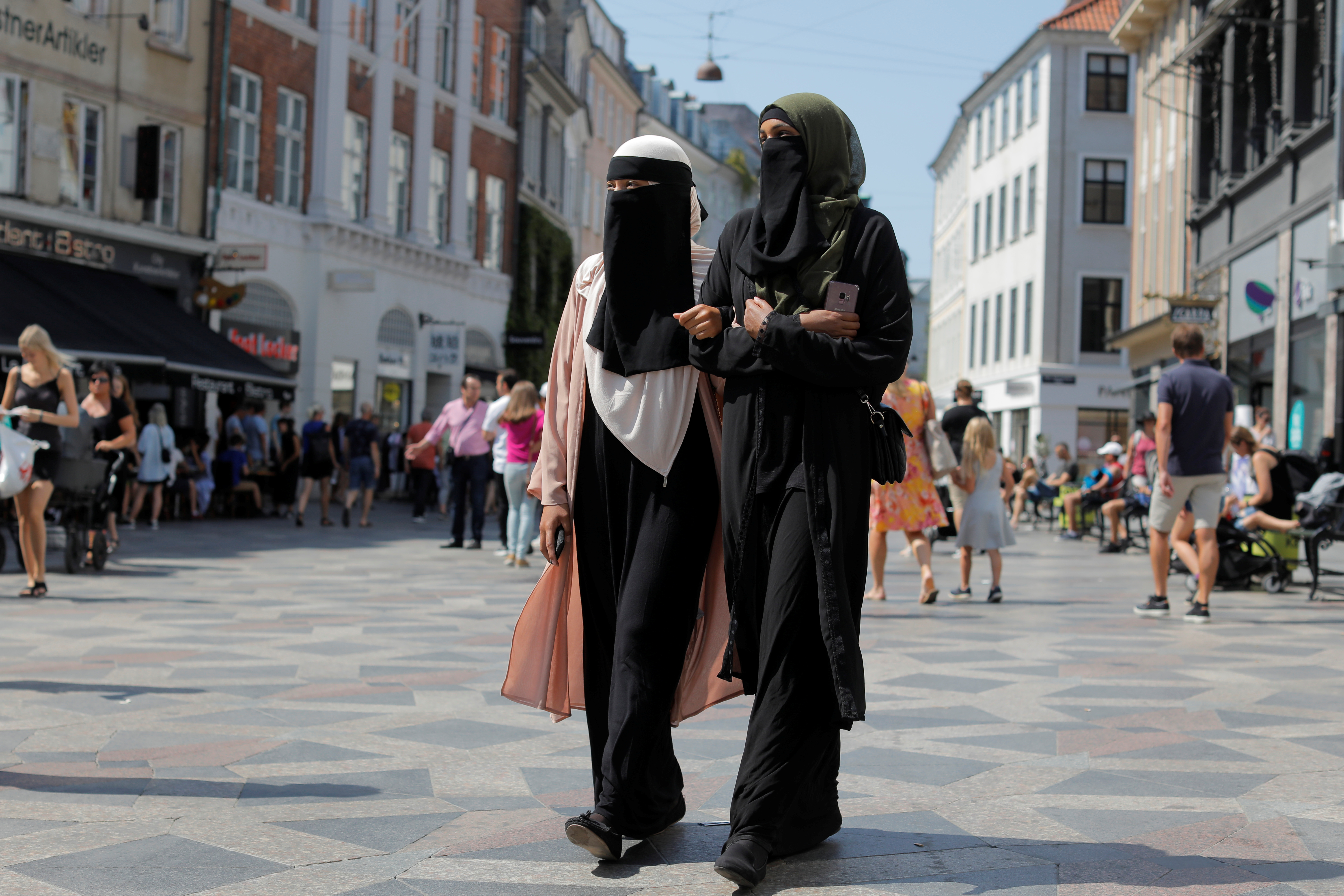 Anna-Bella (L), 26, a home care worker and Amina, 24, a student, both members of the group Kvinder I Dialog (Women in Dialogue) and wearers of the niqab, walk along Stroget, the main shopping strip in Copenhagen, Denmark, July 26, 2018.