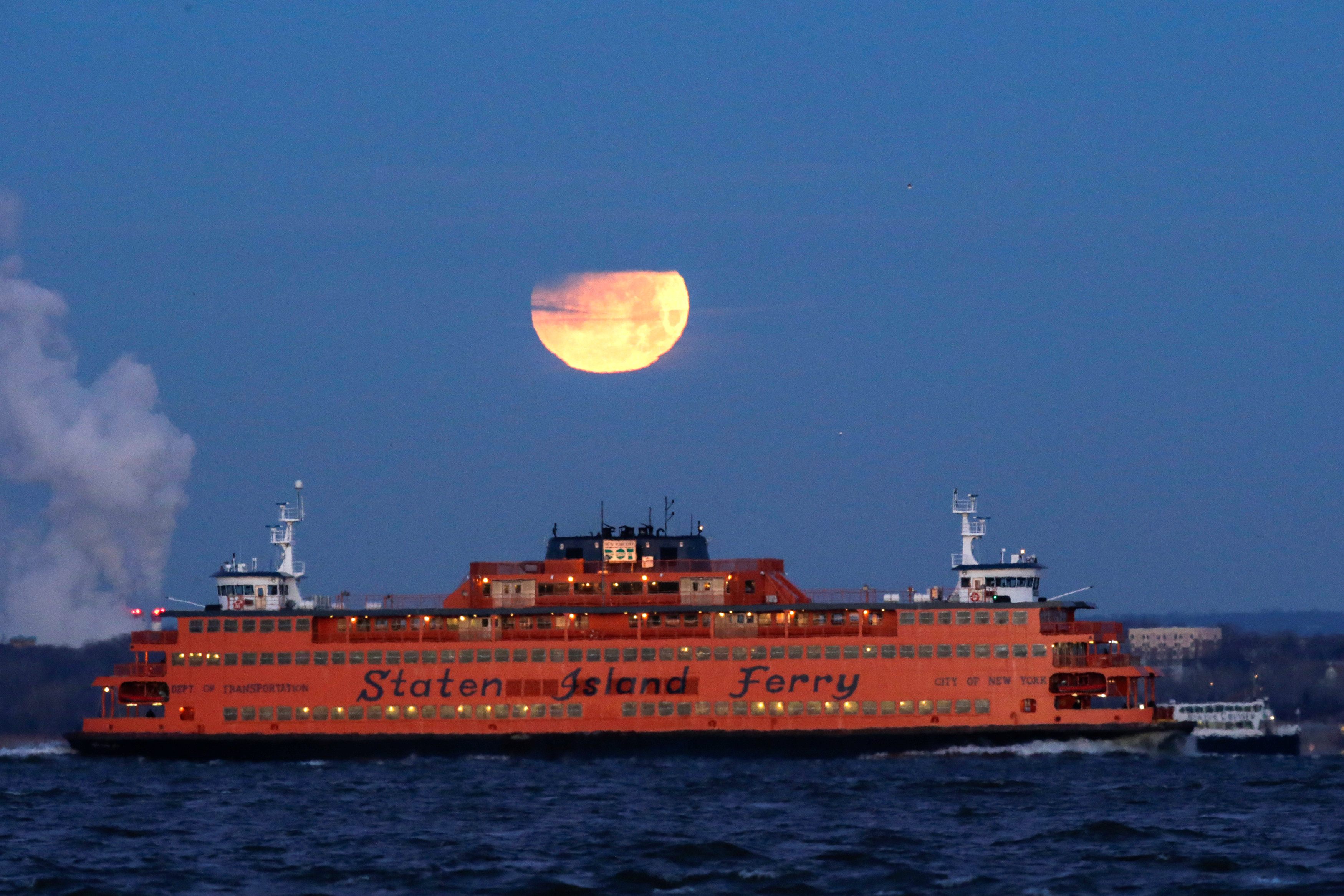 "The ""Super Blue Blood Moon"" sets behind the Staten Island Ferry, seen from Brooklyn, New York, U.S., January 31, 2018."