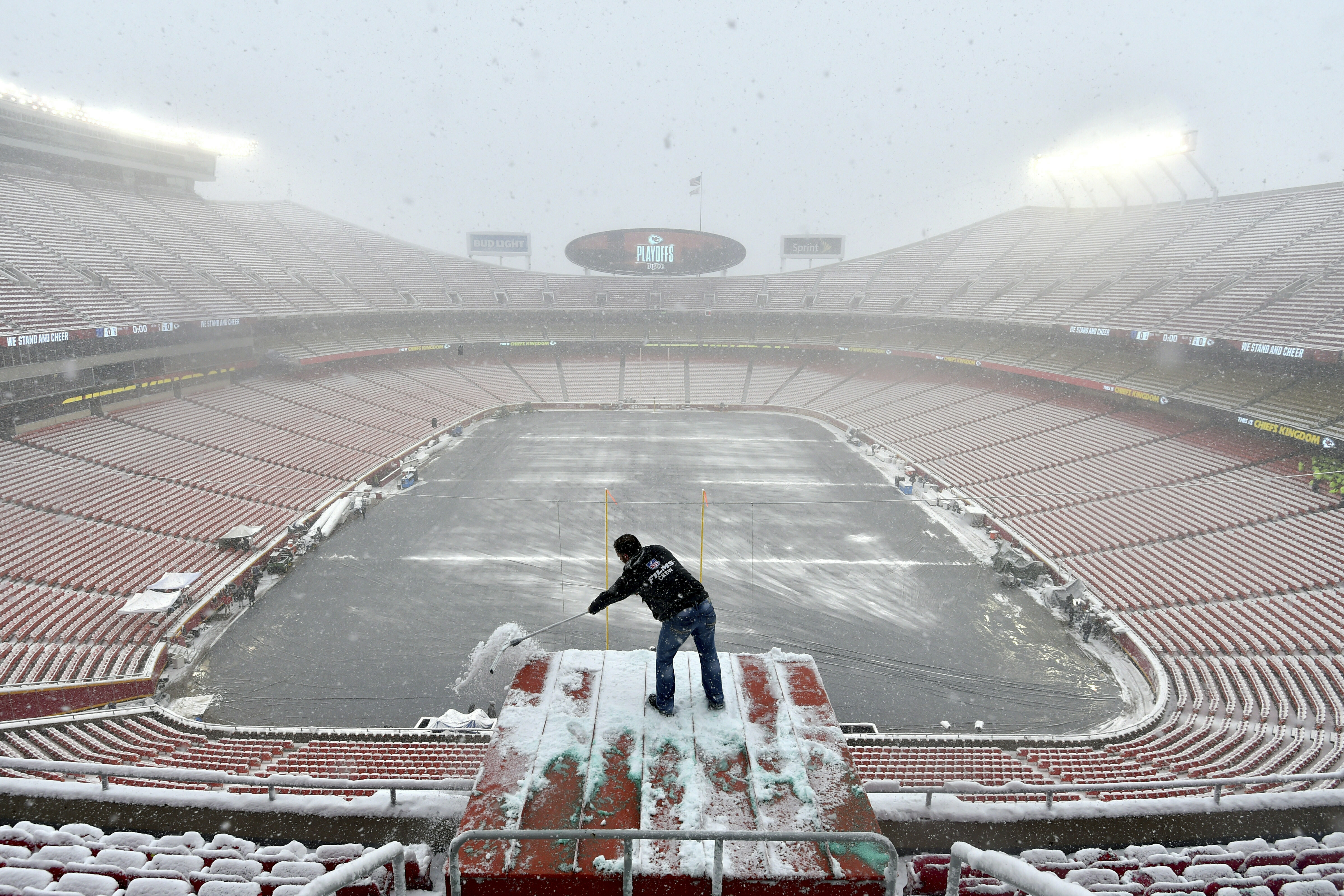 Kyle Haraugh, of NFL Films, clears snow from a camera location at Arrowhead Stadium before an NFL divisional football playoff game between the Kansas City Chiefs and the Indianapolis Colts, in Kansas City, Mo., Jan. 12, 2019.