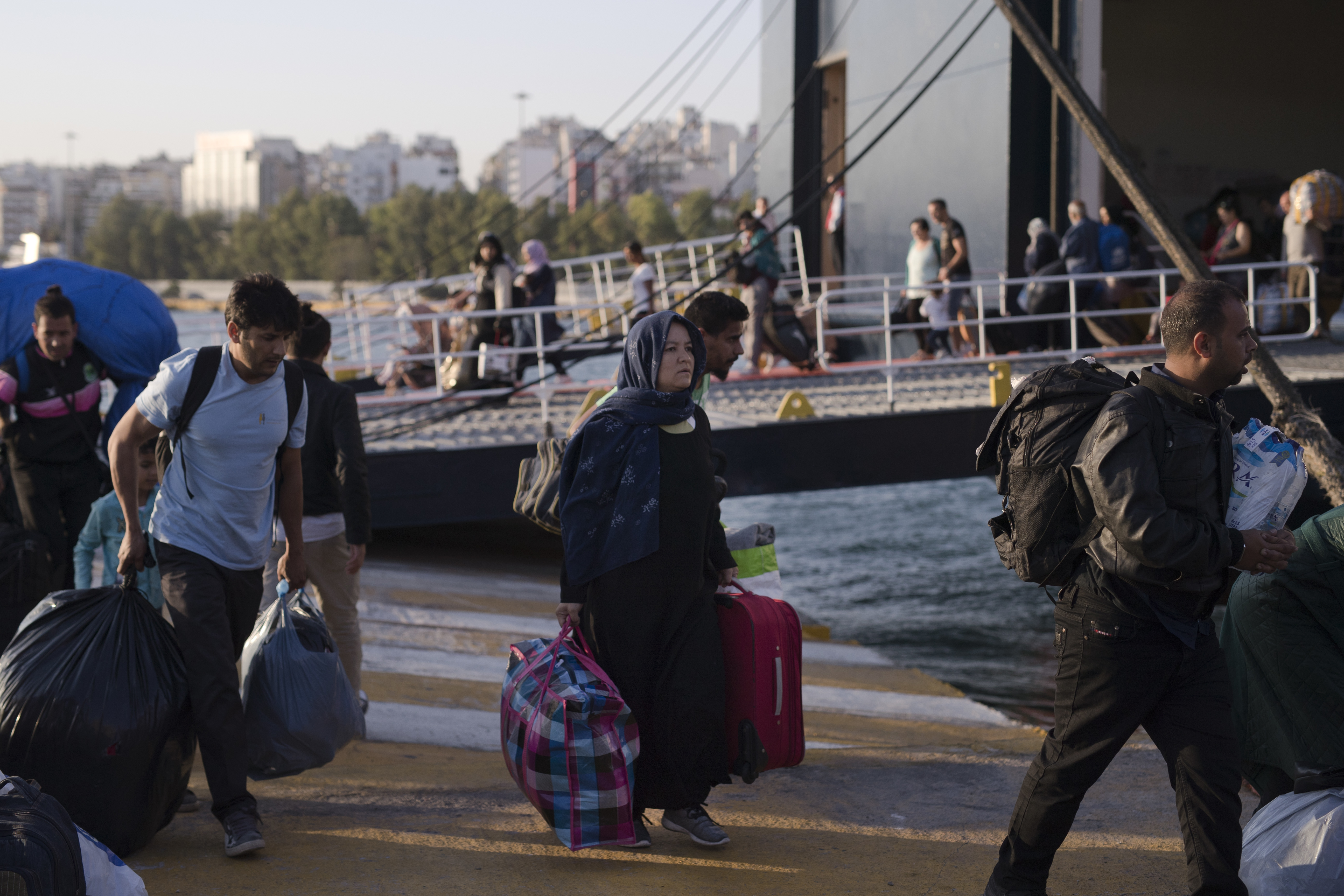 Refugees and migrants carry their belongings after they disembark from a ferry, at the Greece port of Piraeus, near Athens,  Sept. 25, 2018. About 400 migrants and refugees arrived at the port from the island of Lesbos as authorities have been moving...