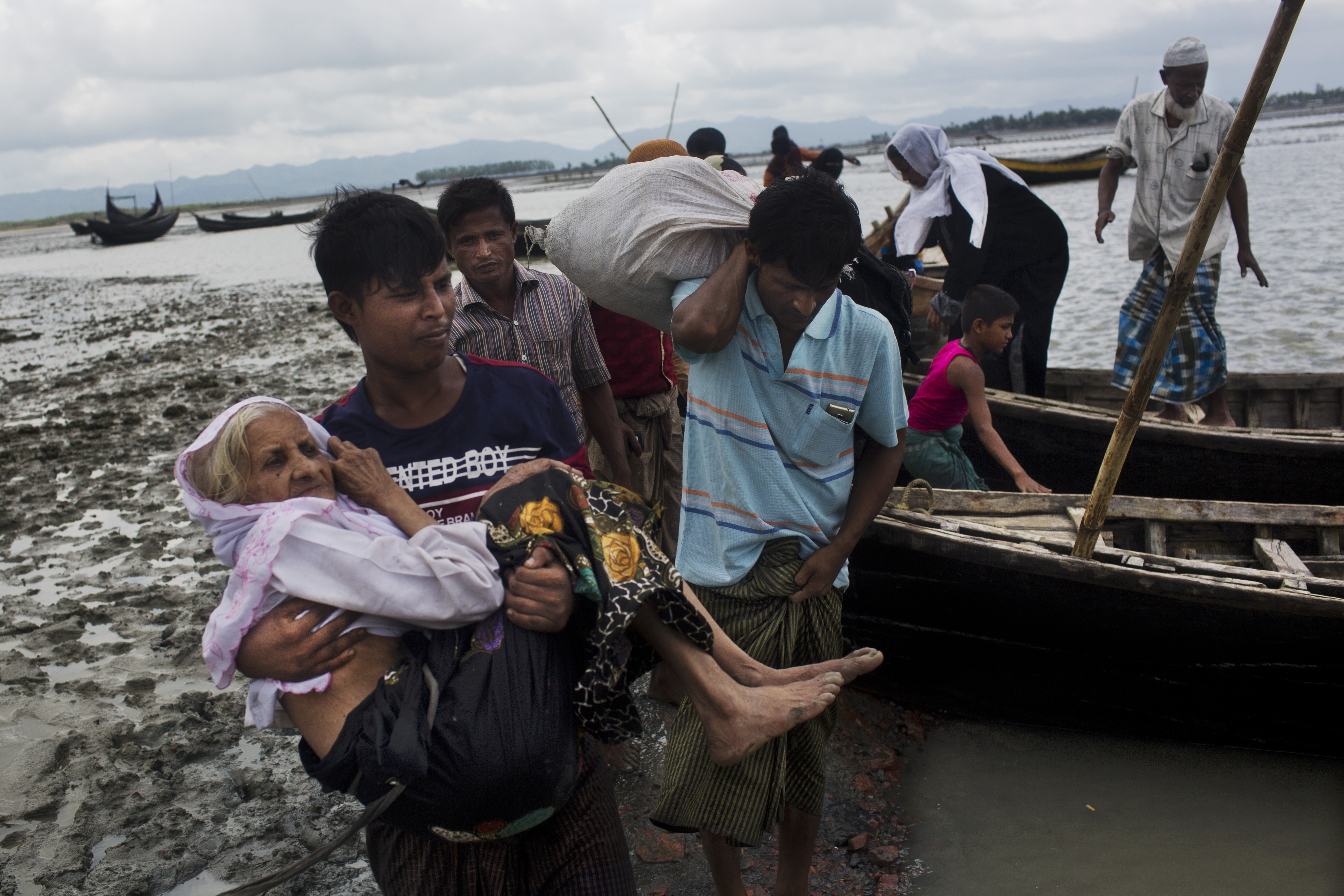 A Rohingya ethnic minority from Myanmar carries an elderly woman as they alight from a local boat on which they crossed a river, after crossing over to the Bangladesh side of the border near Cox's Bazar's Dakhinpara area, Sept. 2, 2017.