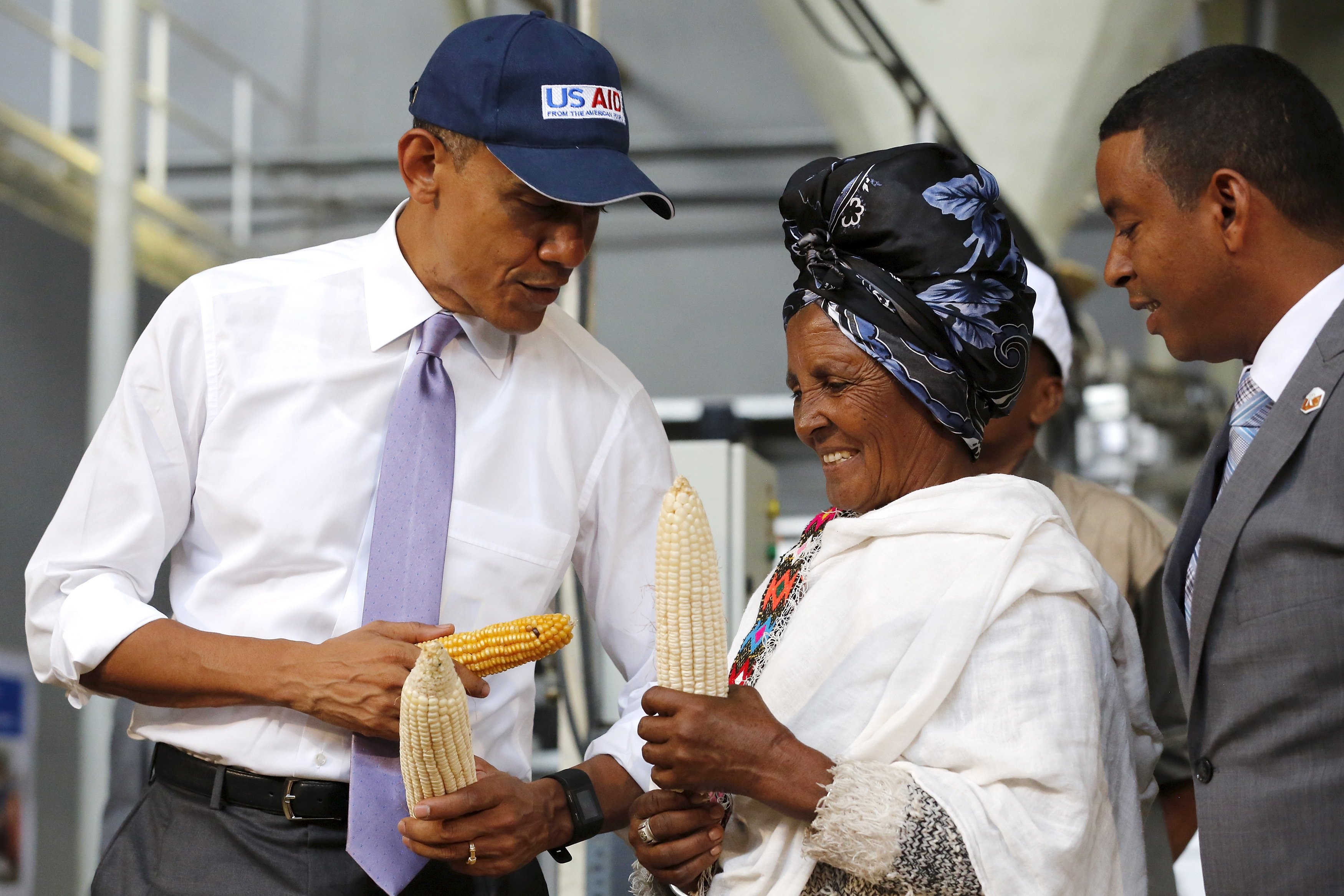U.S. President Barack Obama (L) speaks with a farmer (2nd R) participating in the Feed the Future program as he tours the Faffa Food factory in Addis Ababa, Ethiopia July 28, 2015.
