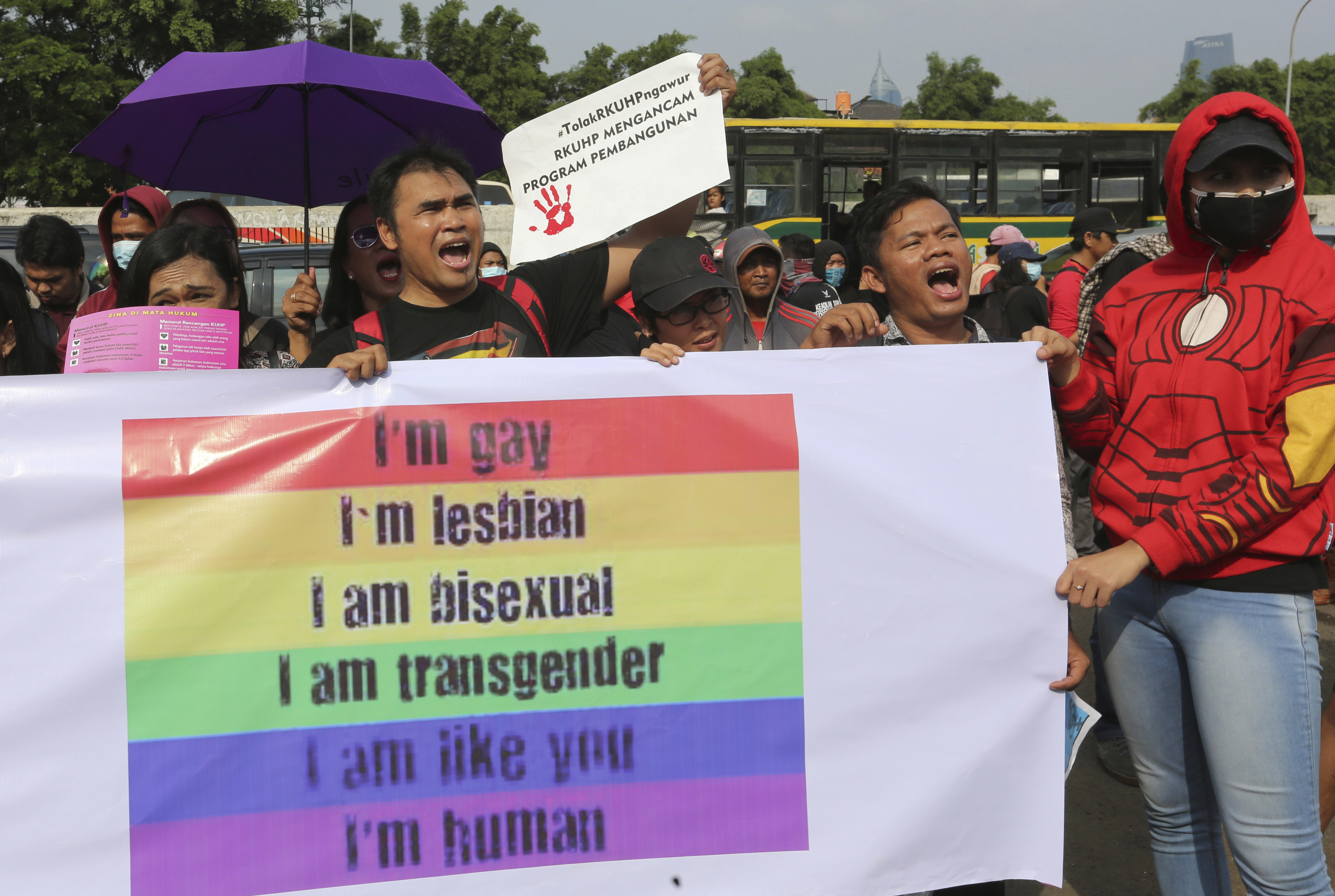 FILE - LGBT activists shout slogans during a rally against a planned revision to Indonesia's criminal code that would criminalize unmarried and gay sex, Feb. 12, 2018, outside the Parliament in Jakarta, Indonesia.