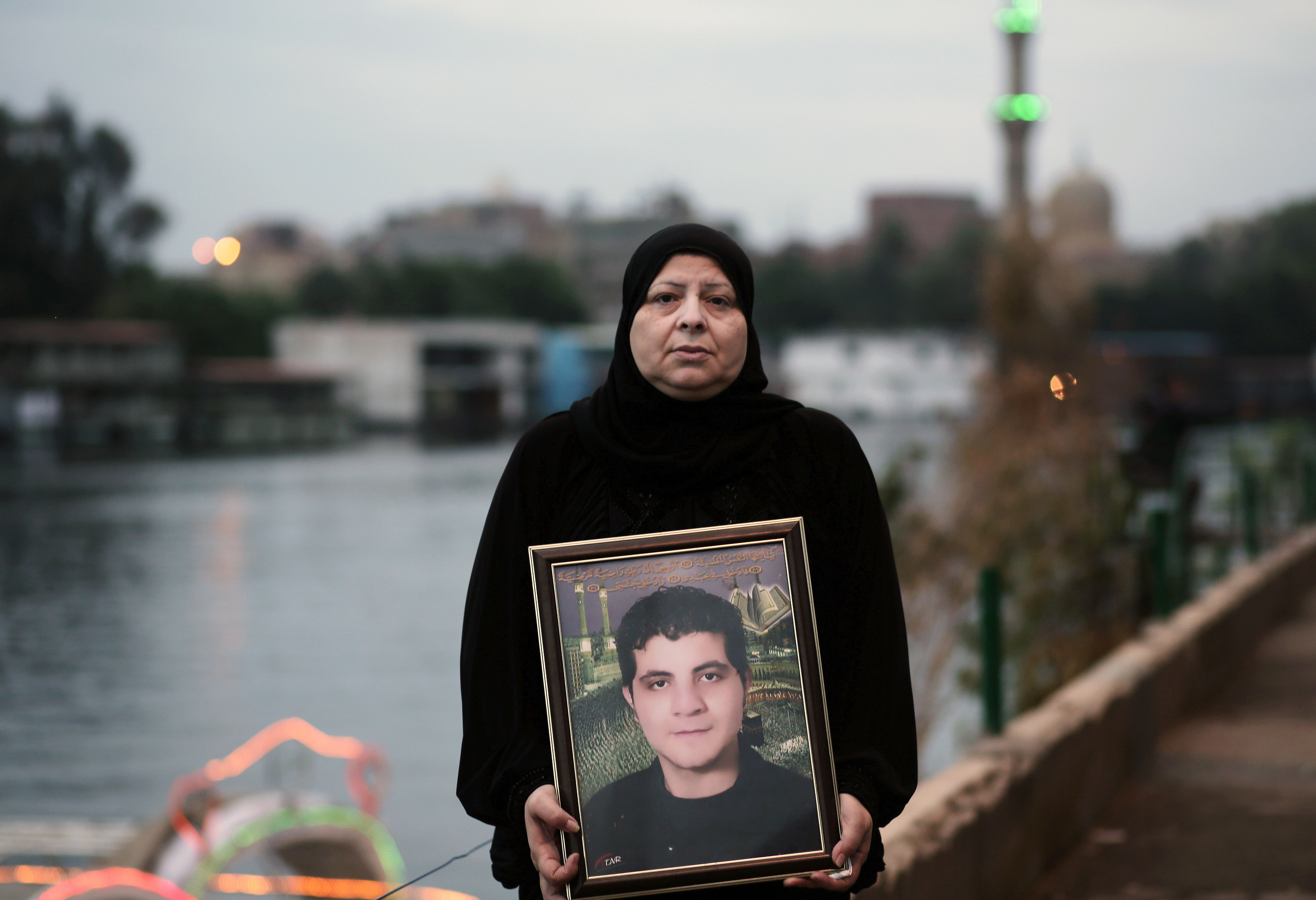 """Amel Shaker holds a portrait of her 25-year-old son Ahmed, who was fatally shot in the back on the """"Friday of Rage,"""" one of the bloodiest days of Egypt's 2011 uprising against longtime autocrat Hosni Mubarak, in Cairo, Egypt."""