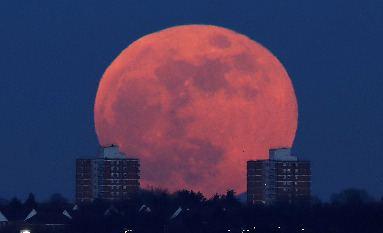 A full moon rises behind blocks of flats in north London, Britain, Jan. 31, 2018.