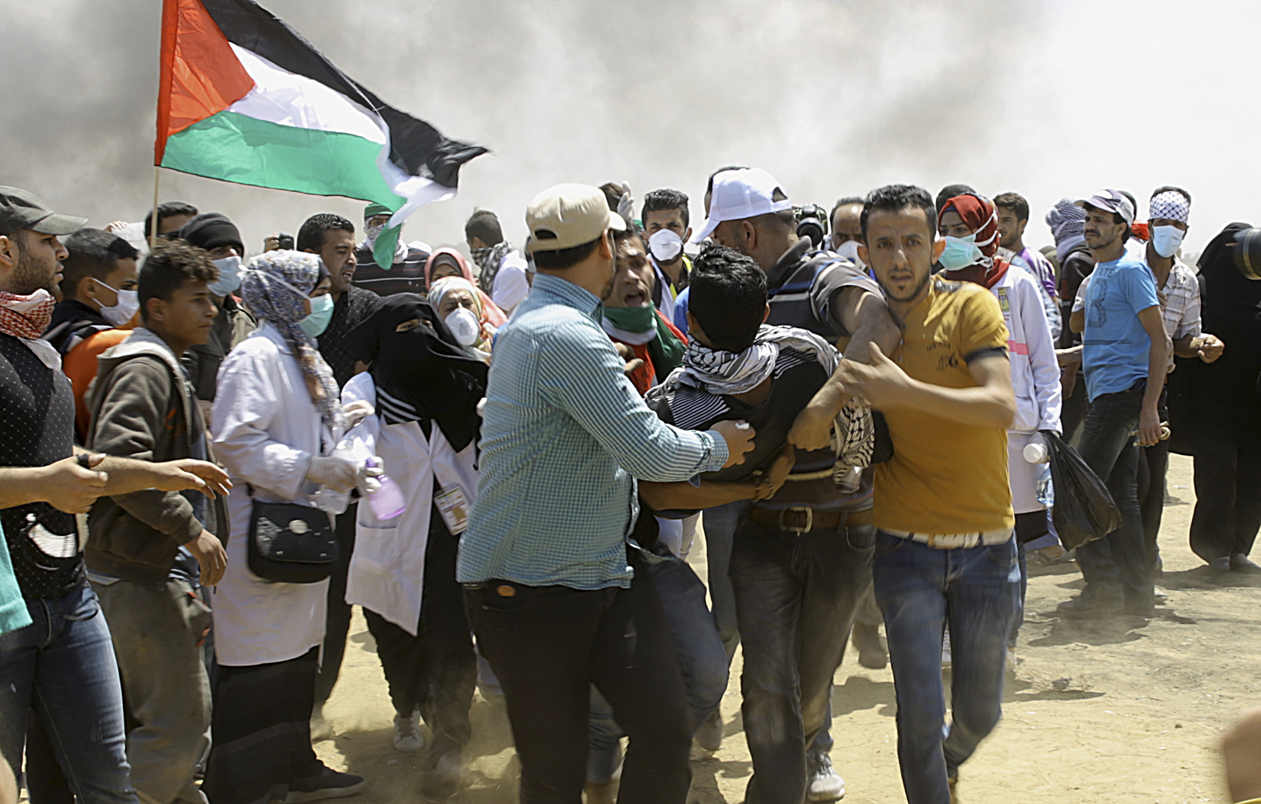 Palestinian protesters evacuate a wounded youth near the Israeli border fence, east of Khan Younis, in the Gaza Strip, May 14, 2018.