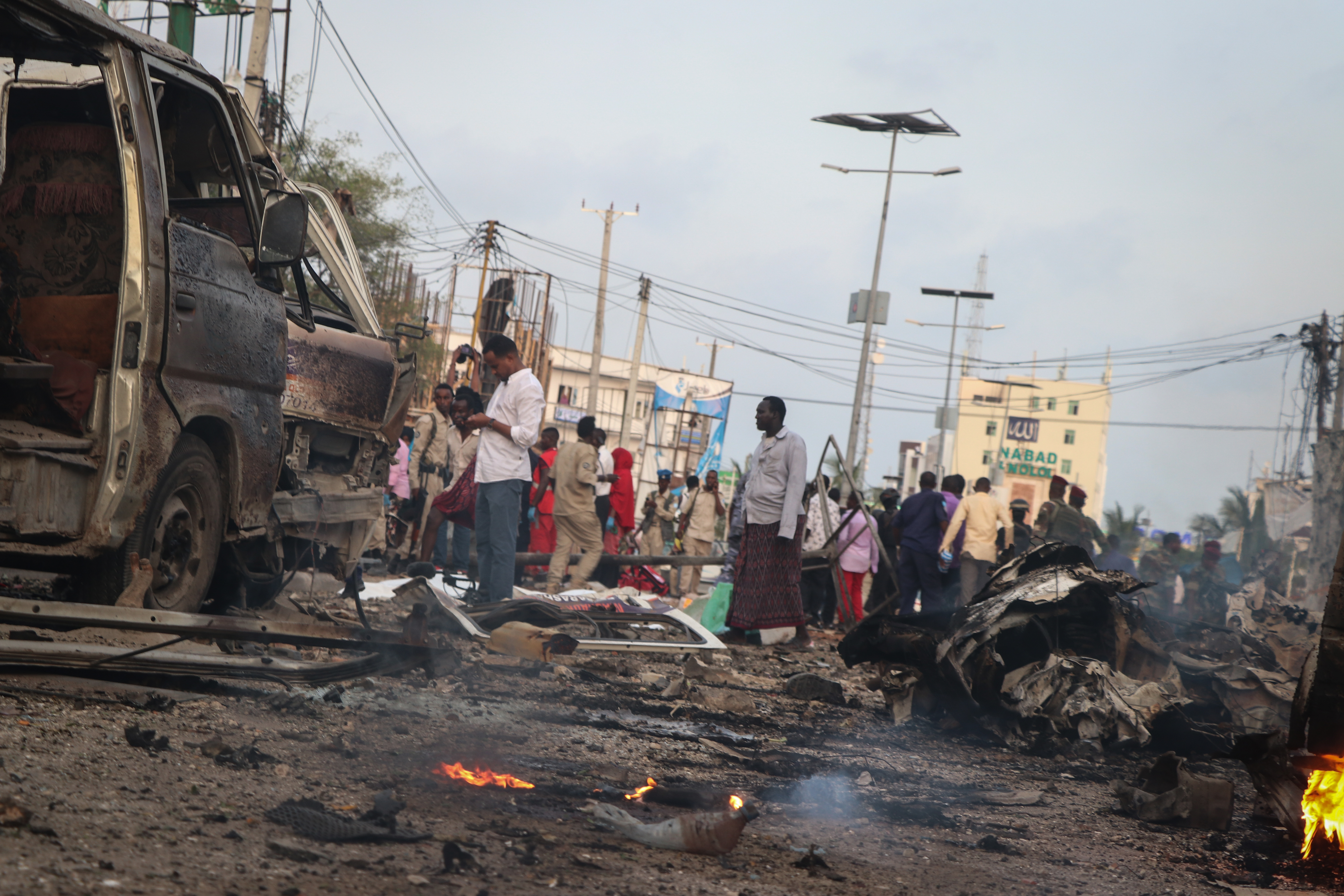 People gather at the scene of twin car bombs that exploded within moments of each other in the Somali capital Mogadishu, Nov. 9, 2018, near a popular Sahafi hotel in the Somali capital Mogadishu.