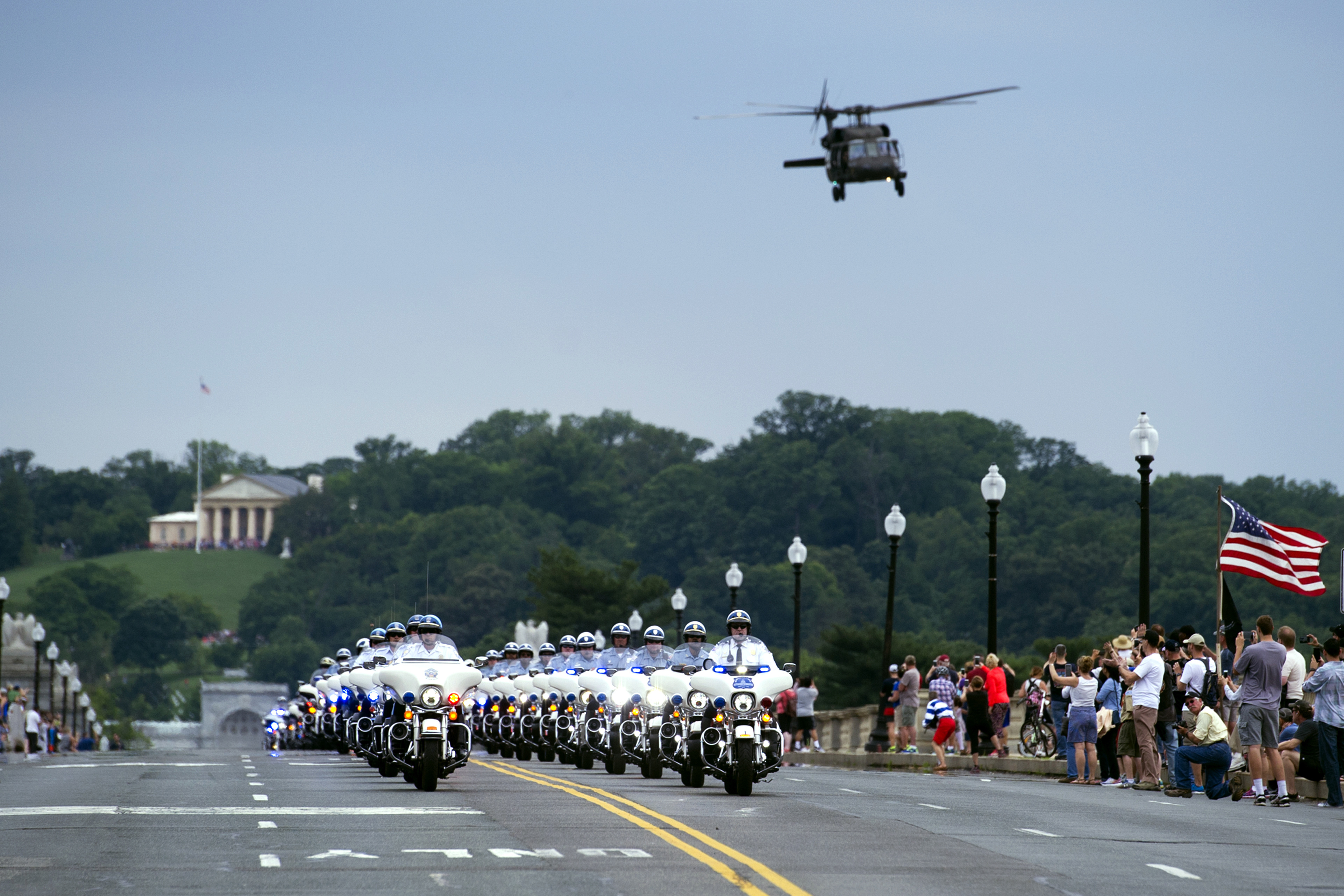 A military helicopter flies over a police escort on the Memorial Bridge, for motorcyclists riding in the 30th anniversary of the Rolling Thunder 'Ride for Freedom' demonstration in Washington, May 28, 2017.