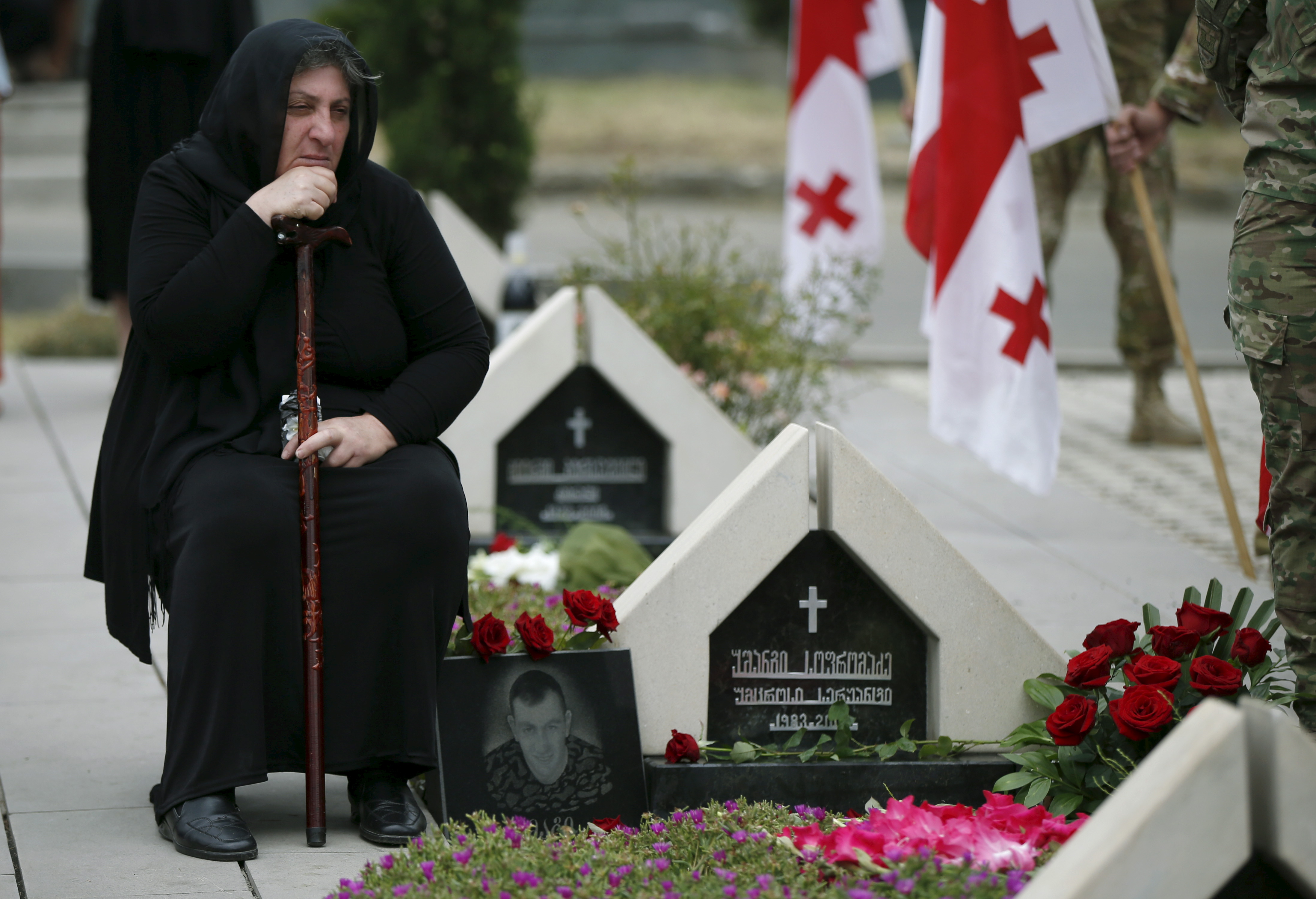 FILE - A woman mourns at the grave of a Georgian soldier killed during Georgia's conflict with Russia over the breakaway region of South Ossetia in 2008 during a ceremony at the memorial cemetery in Tbilisi, Georgia, Aug. 8, 2015.