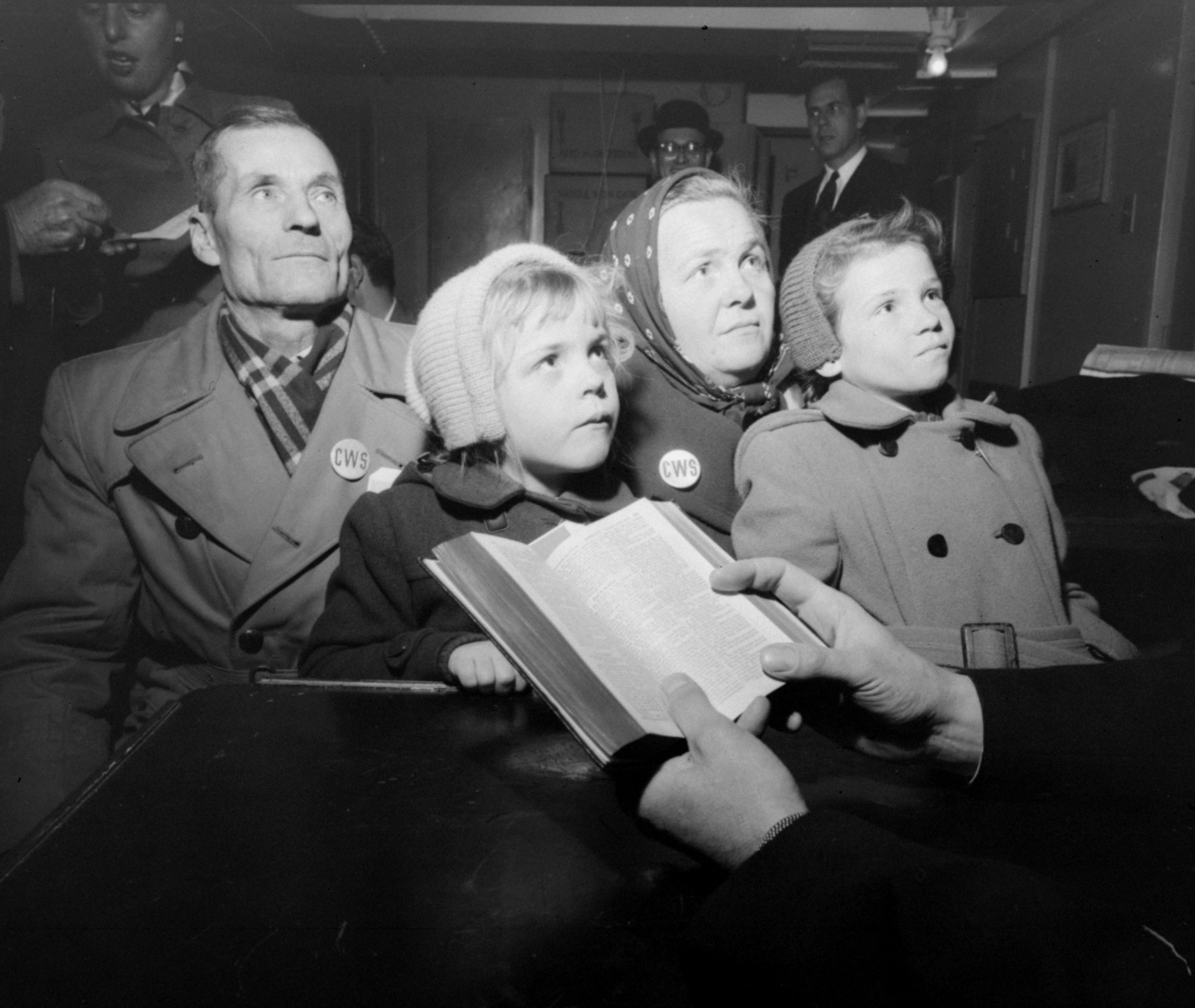 FILE - Kusma Kandaurow, 61, and his wife, Sofie, 41, and their children, Hanna, left, front, 9, and Sonja, 5, are in deep thought as a clergyman reads scripture following their arrival in New York City, Dec. 16, 1955, with other refugees aboard the N...