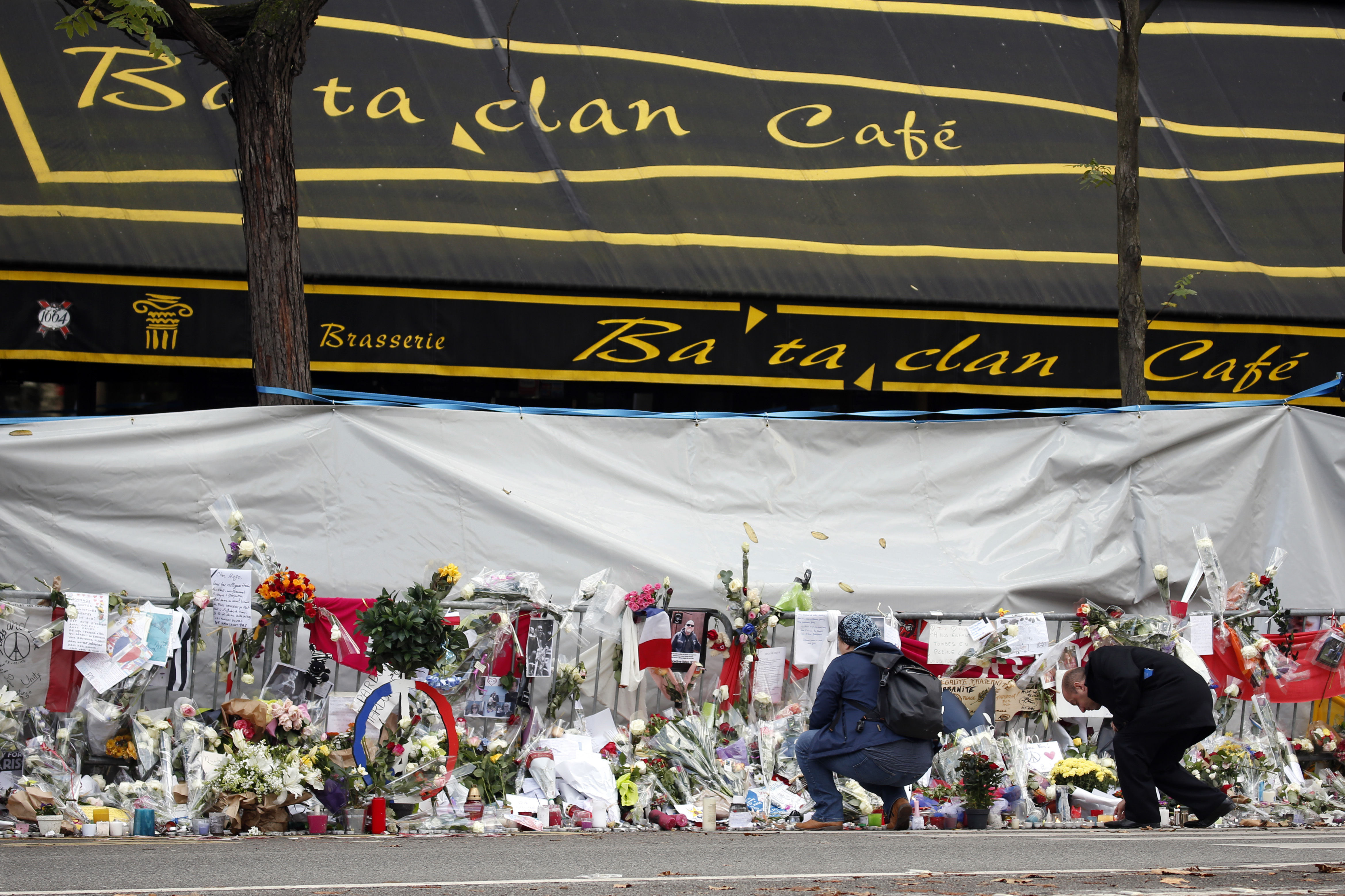 People mourn in front of the screened-off facade of the Bataclan Cafe adjoining the concert hall, one of the sites of the deadly attacks in Paris, France, a day before a ceremony to pay tribute to the 130 victims, Nov. 26, 2015.