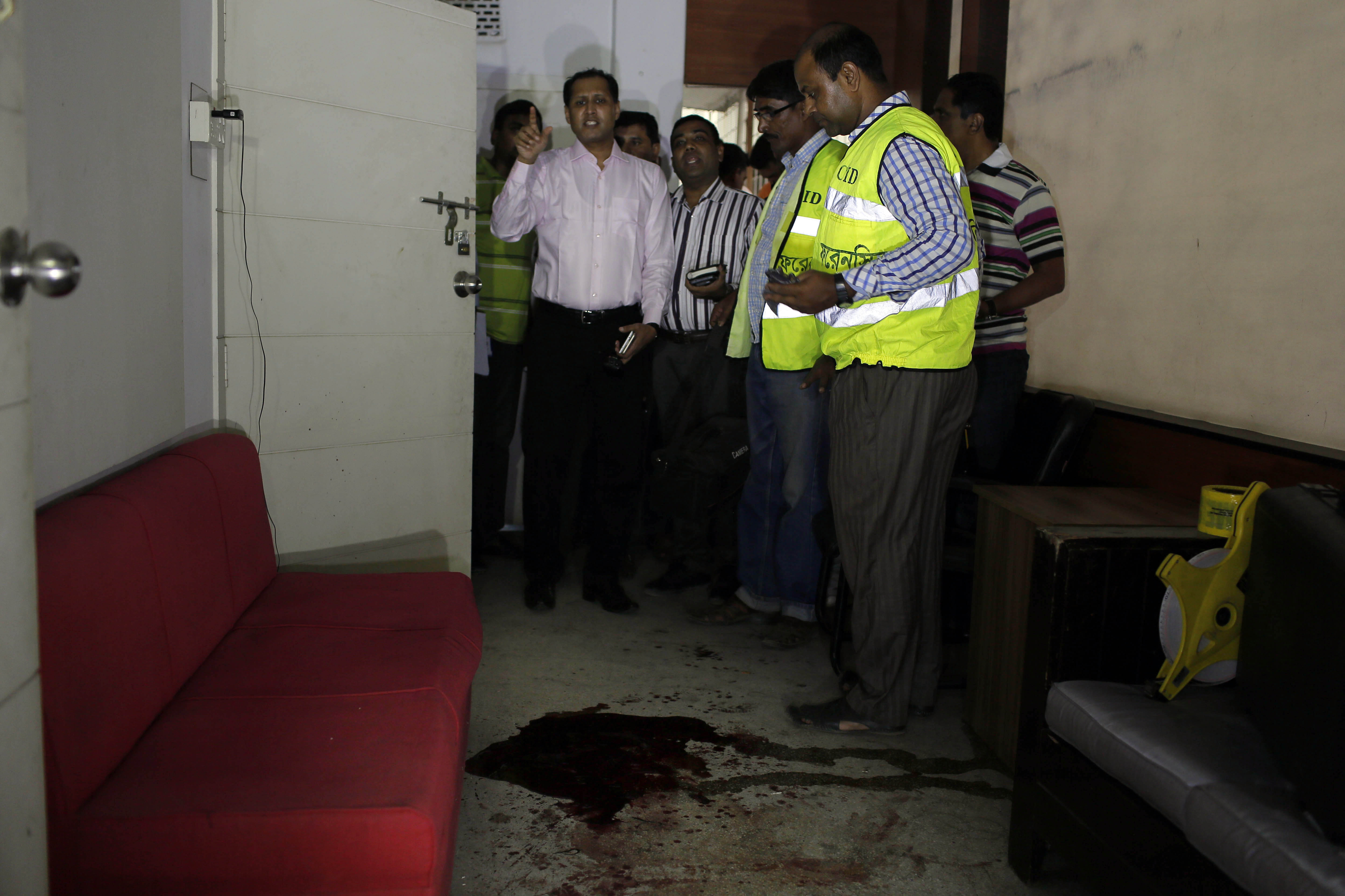 Bangladeshi security officers inspect the blood-stained site where publisher Ahmed Rahim Tutul and two writers were shot and stabbed by assailants in the office of the Shudhdhoswar publishing house, in Dhaka, Bangladesh, Oct. 31, 2015.