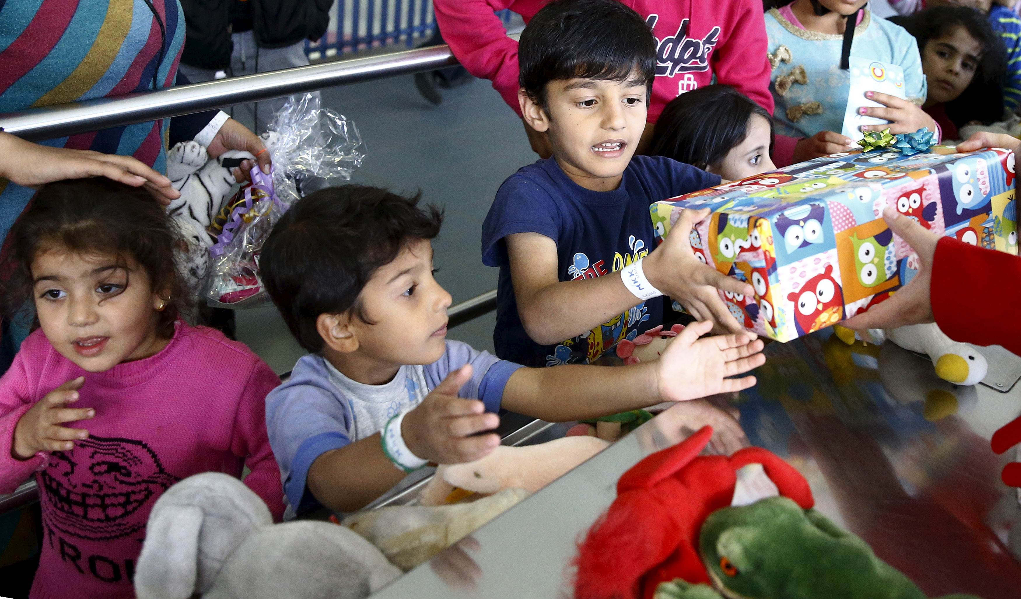 Migrant children reach out for gifts donated by the local community for the Bayram festivities at an improvised temporary shelter in a sports hall in Hanau, Germany, Sept. 24, 2015.