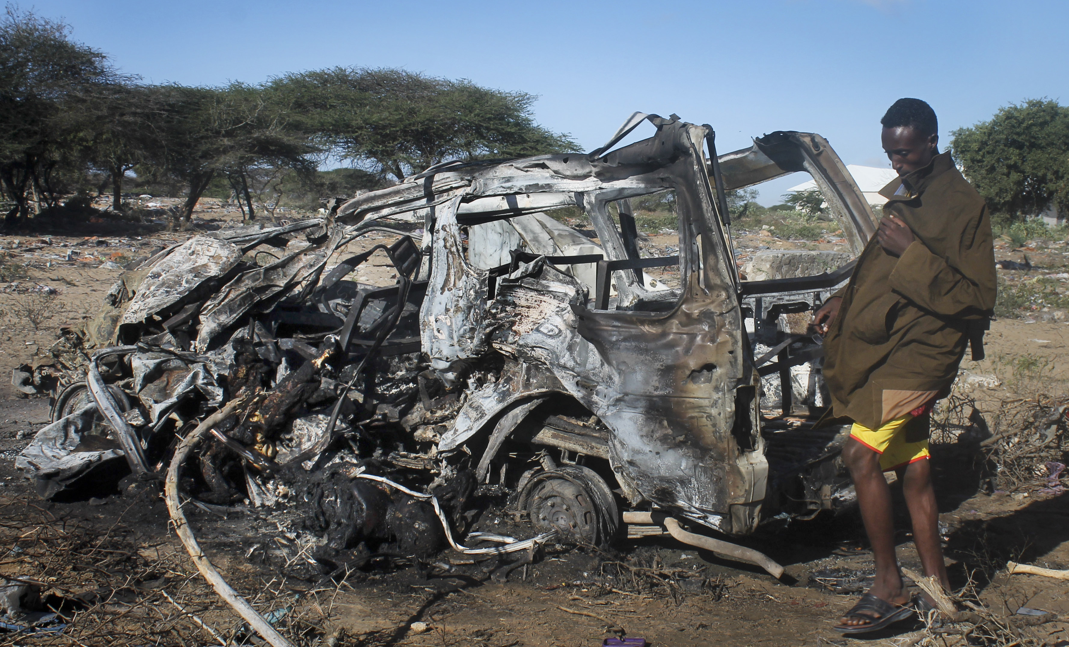 FILE - A Somali soldier stands near a vehicle destroyed by a suicide car bomb attack near the Elasha Biyaha settlement south of Mogadishu, Somalia — an attack that followed the killing of al-Shabab's top leader in a U.S. airstrike, Sept. 8, 2014.