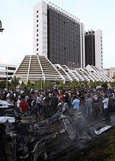 People stand near destroyed cars after an explosion at Tibesti hotel in Benghazi, Libya June 1, 2011