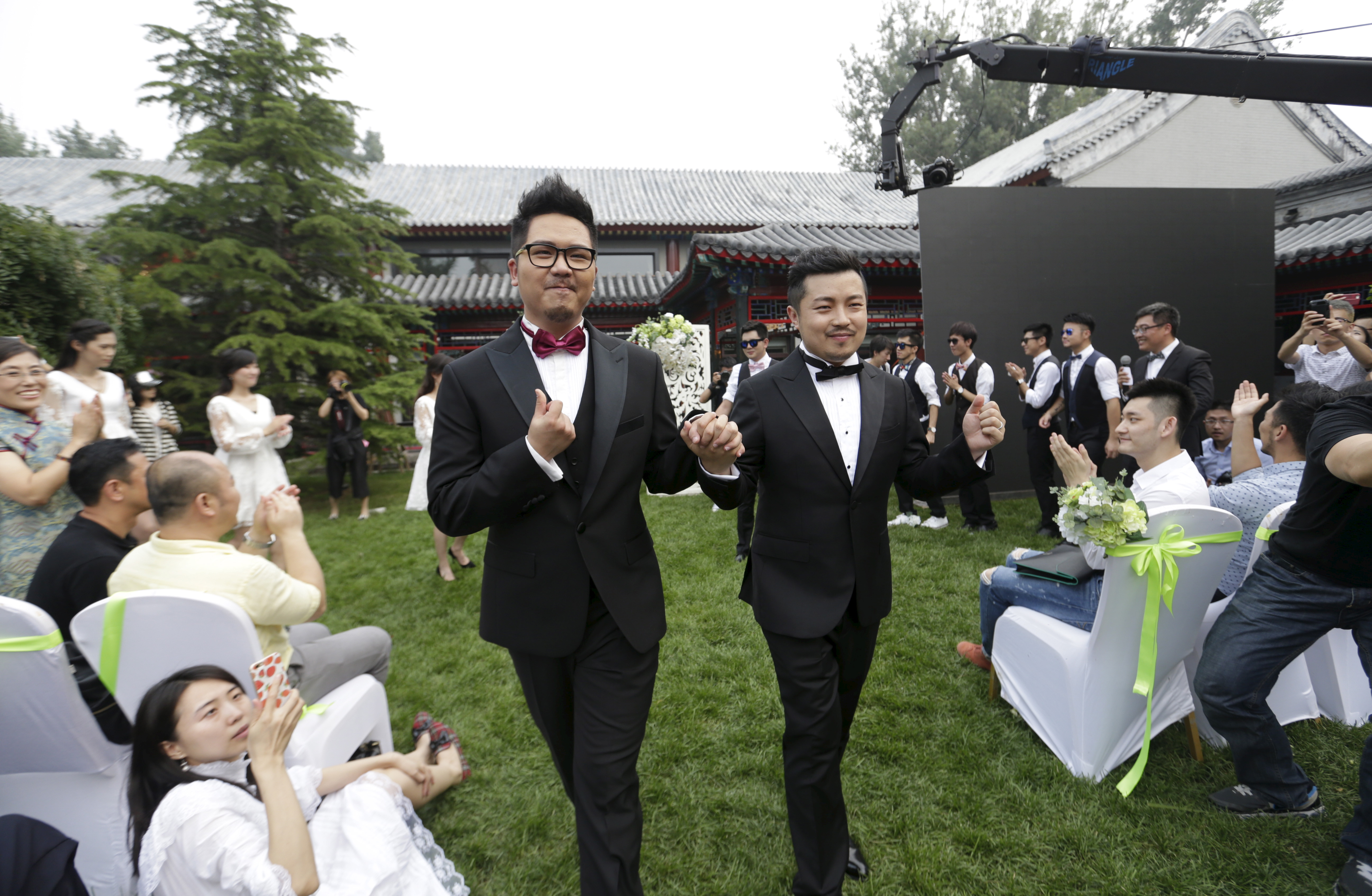 FILE - Gino, left, and Ling Jueding leave after their wedding at a park in Beijing, June 27, 2015. The gay couple had to change the venue for their ceremony nearly 10 times because of intervention from local police. Same-sex marriage is illegal in Ch...