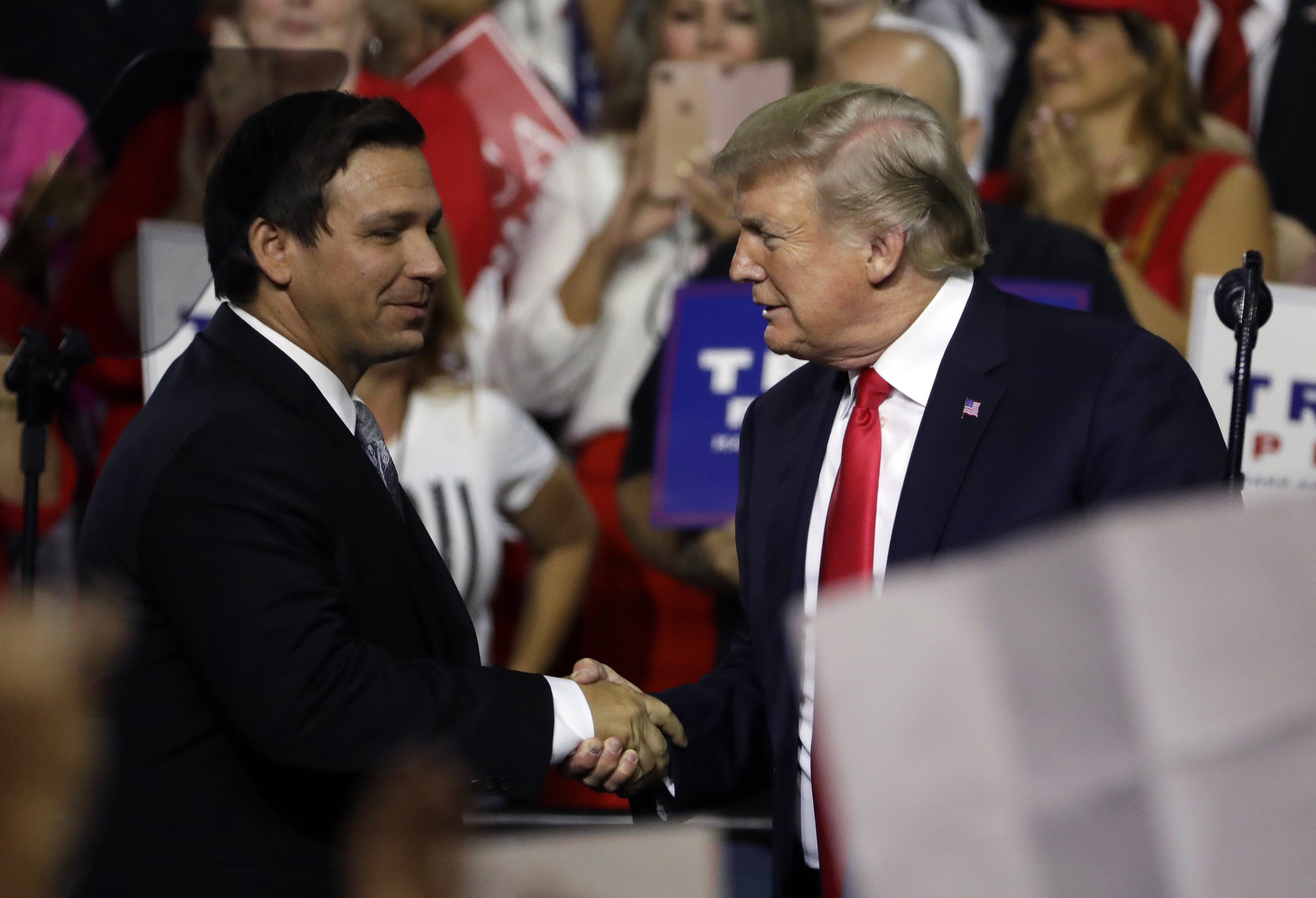President Donald Trump, right, shakes hands with Florida Republican gubernatorial candidate Ron DeSantis during a rally in Tampa, Fla., July 31, 2018.