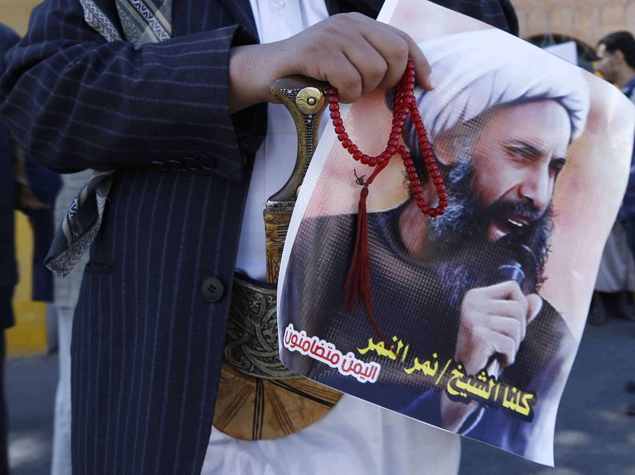 A Shi'ite protester carries a poster of Sheikh Nimr al-Nimr during a demonstration outside the Saudi embassy in Sanaa, Oct. 18, 2014.