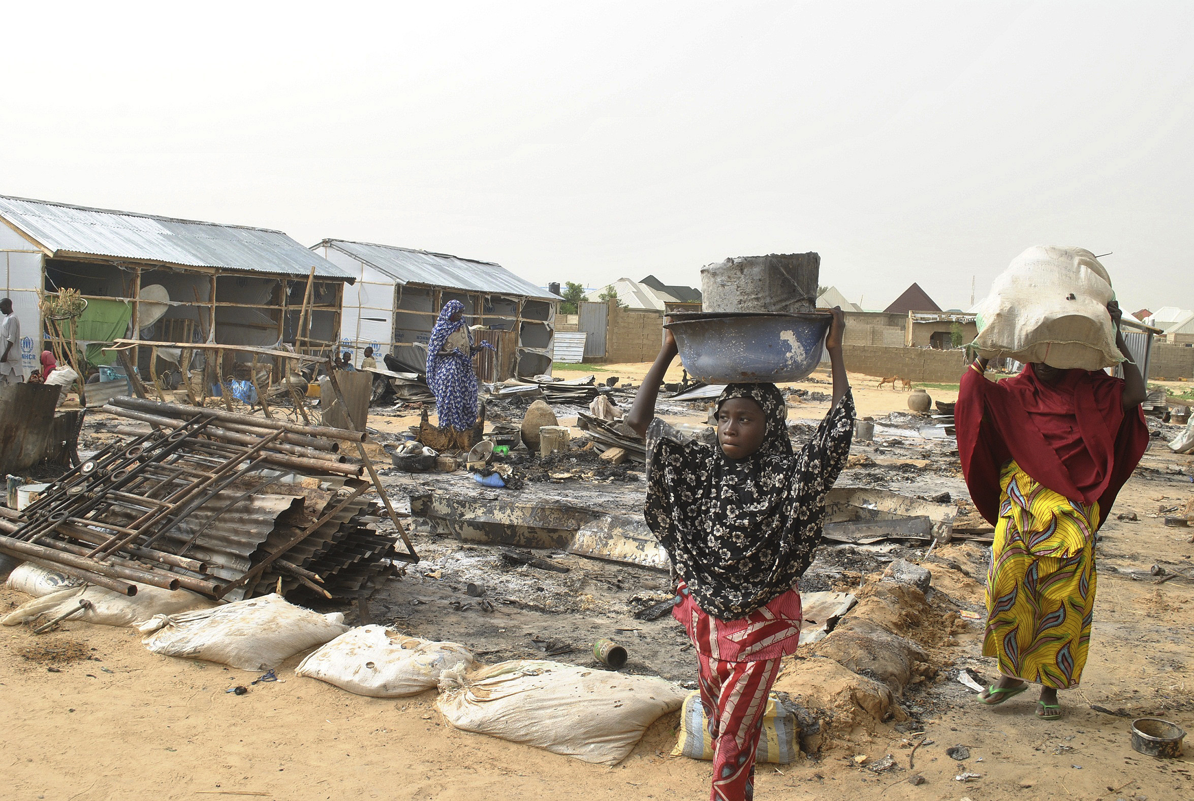 People walk through the debris at a camp for people displaced following an explosion by Islamist extremists, in Maiduguri, Nigeria, June  8, 2017.