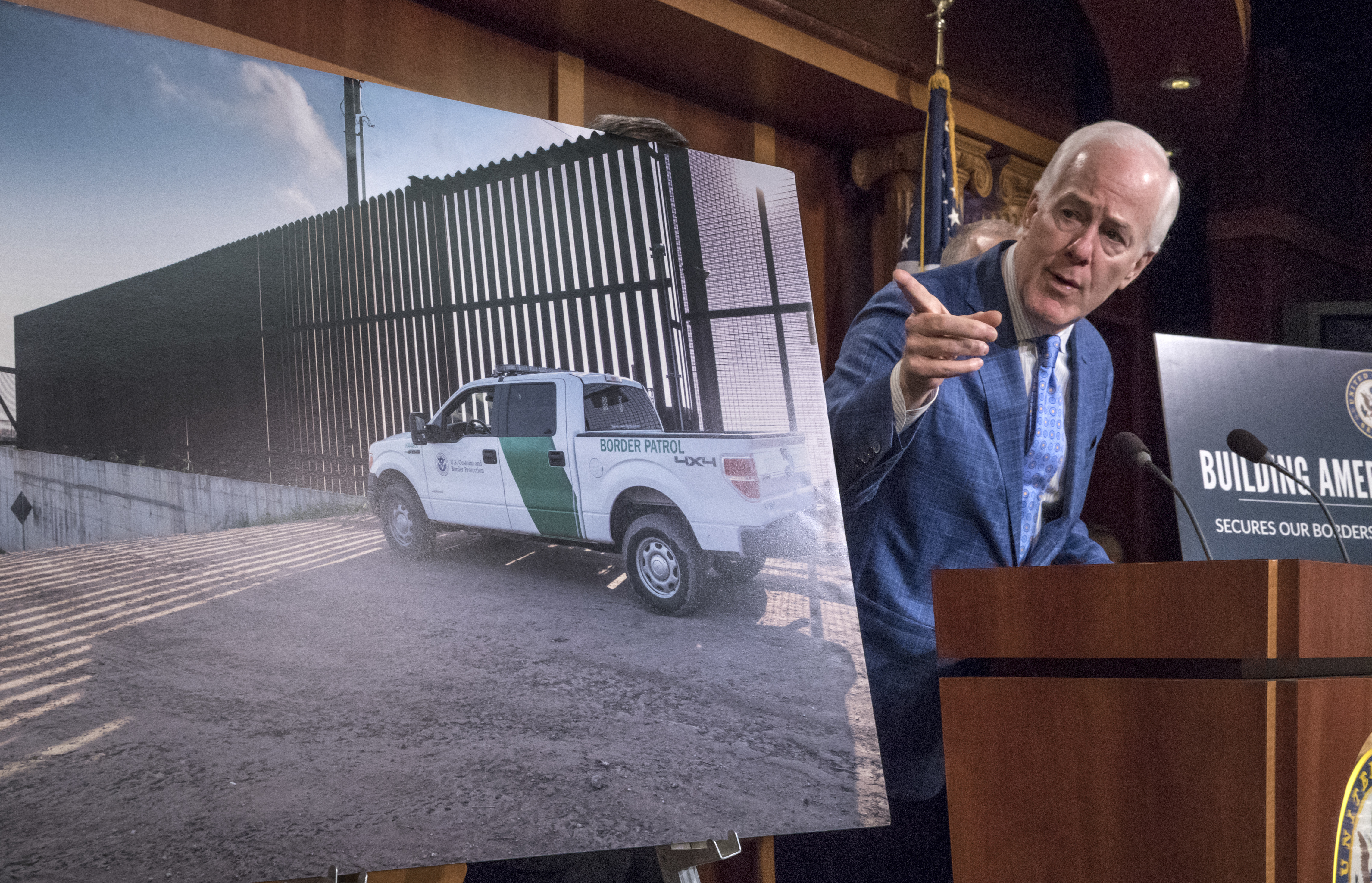Senate Majority Whip John Cornyn of Texas points to a poster as he talks to reporters about border security on Capitol Hill, Washington, Aug. 3, 2017.