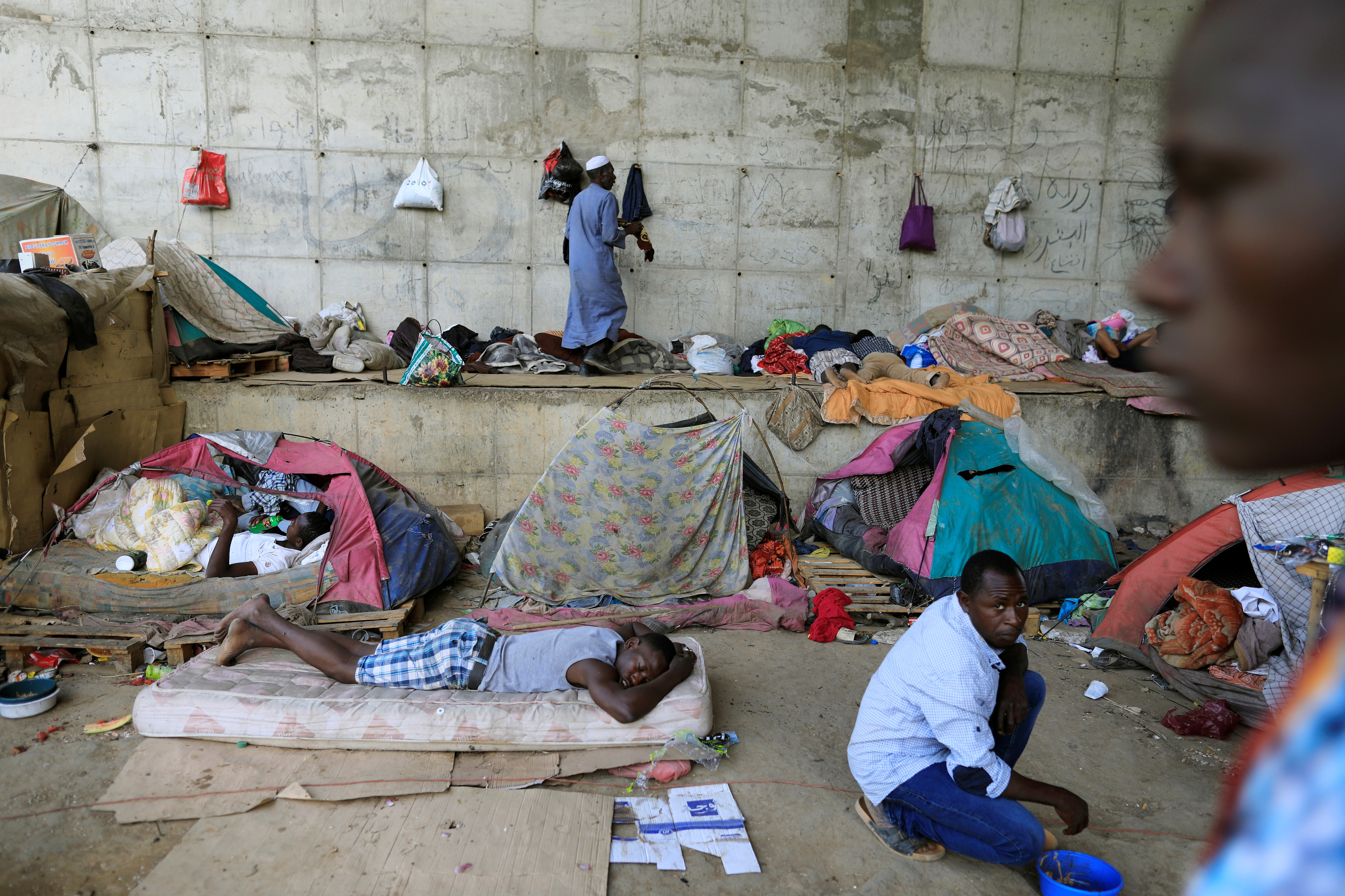 FILE - African migrants take shelter under the bridge of a motorway on the outskirts of Algiers, Algeria, June 28, 2017.