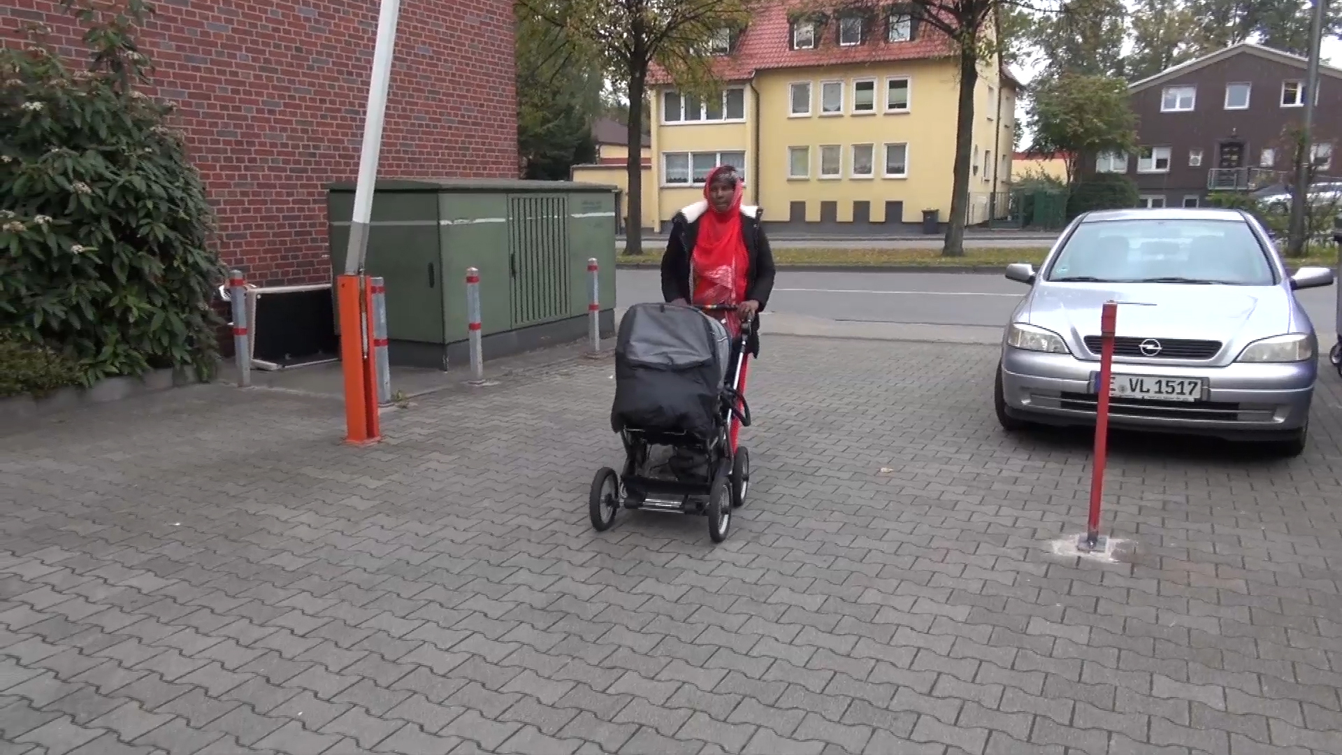 Somali migrant mother Rahma Abukar Ali walks her baby daughter, Sophia, in a stroller at a refugee center in a small German town near Duesseldorf, where she is awaiting a response to her application for asylum, Oct. 2015. (A. Osman/VOA)