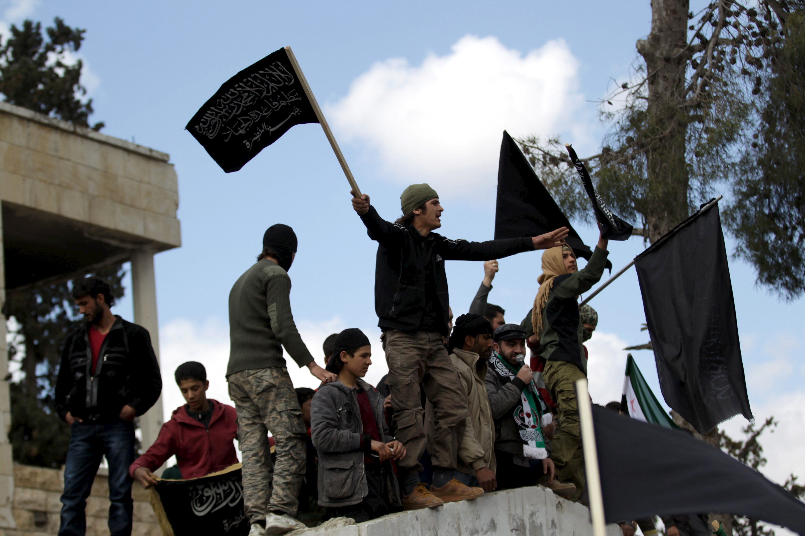 Protesters carry Nusra Front flags and shout slogans during an anti-government protest after Friday prayers in the town of Marat Numan in Idlib province, Syria, March 11, 2016.