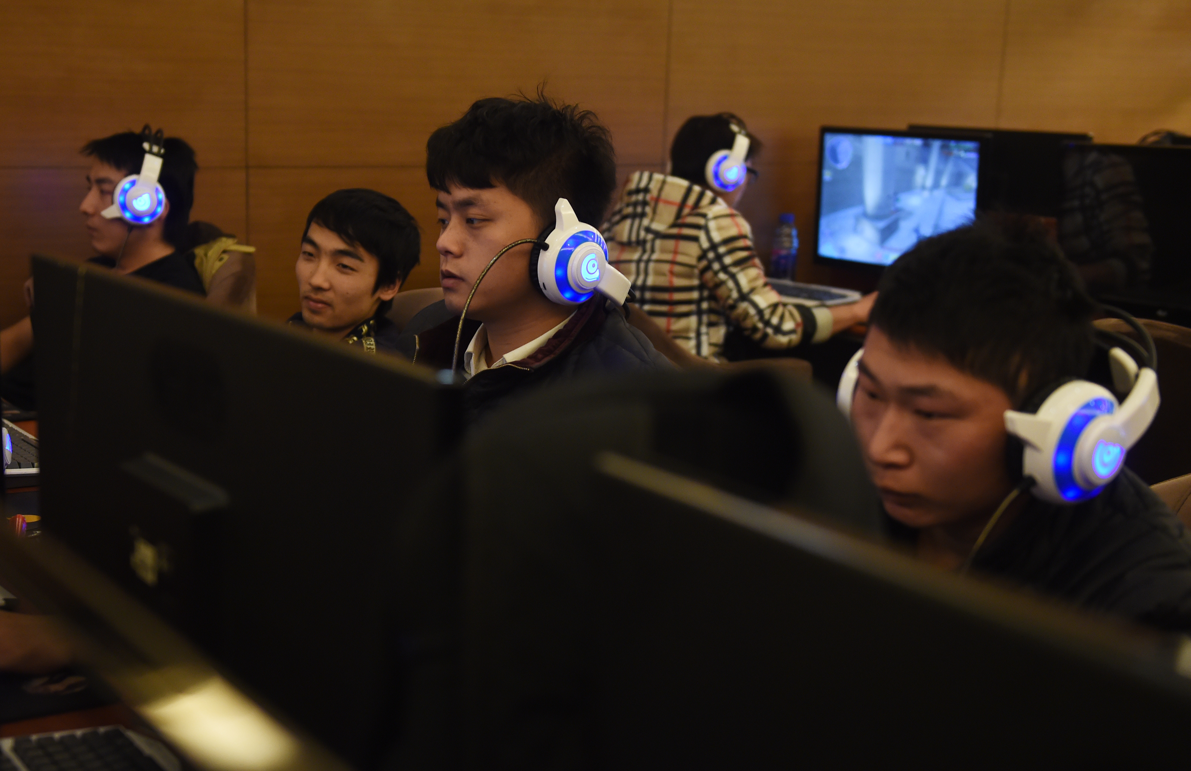 FILE - Young men sit at computers at an internet cafe in Beijing, China, Dec. 16, 2015.
