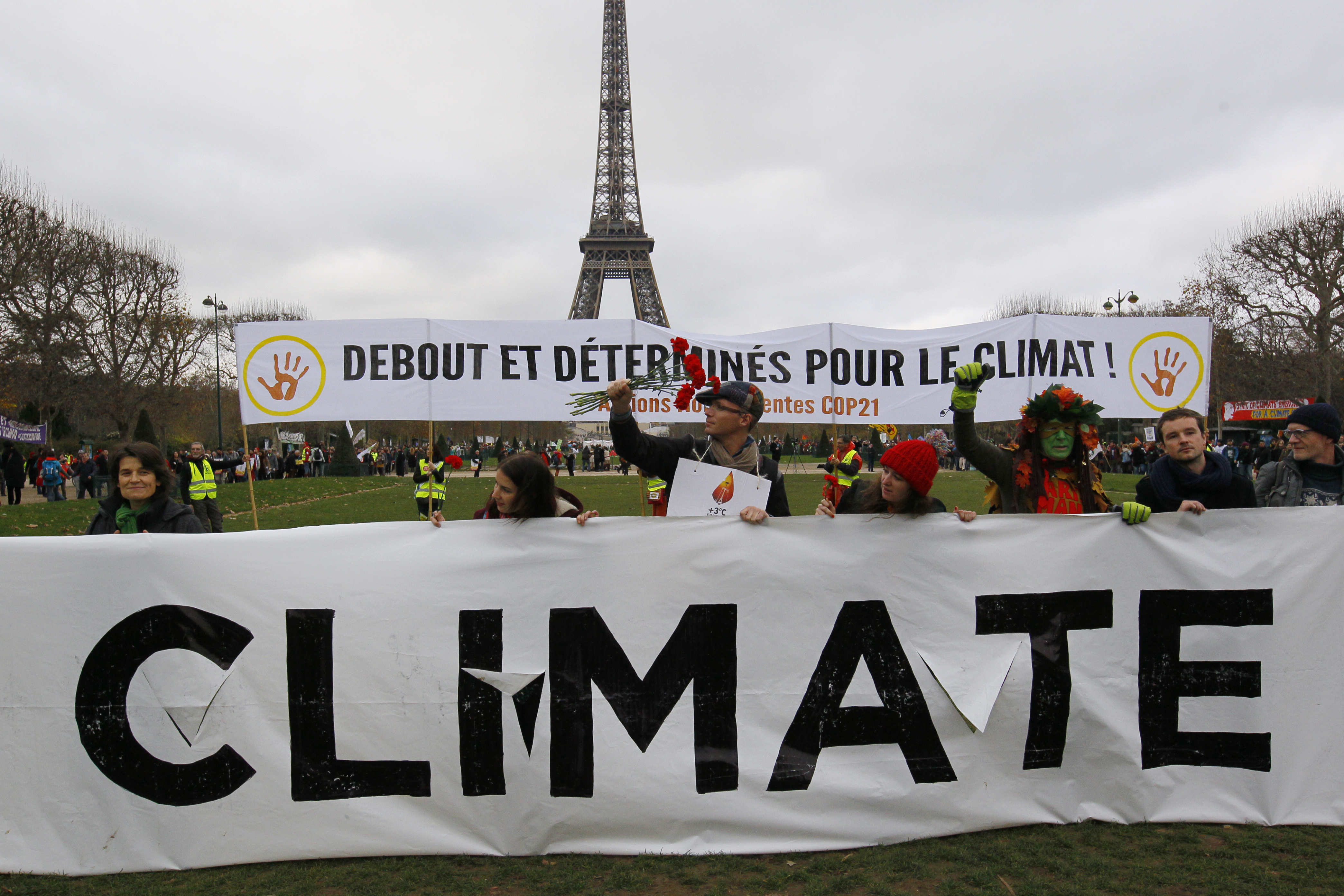 """Environmentalists hold a banner that reads """"Standing and Determined for the Climate"""" at a climate conference protest demonstration near the Eiffel Tower in Paris, France, Dec. 12, 2015."""