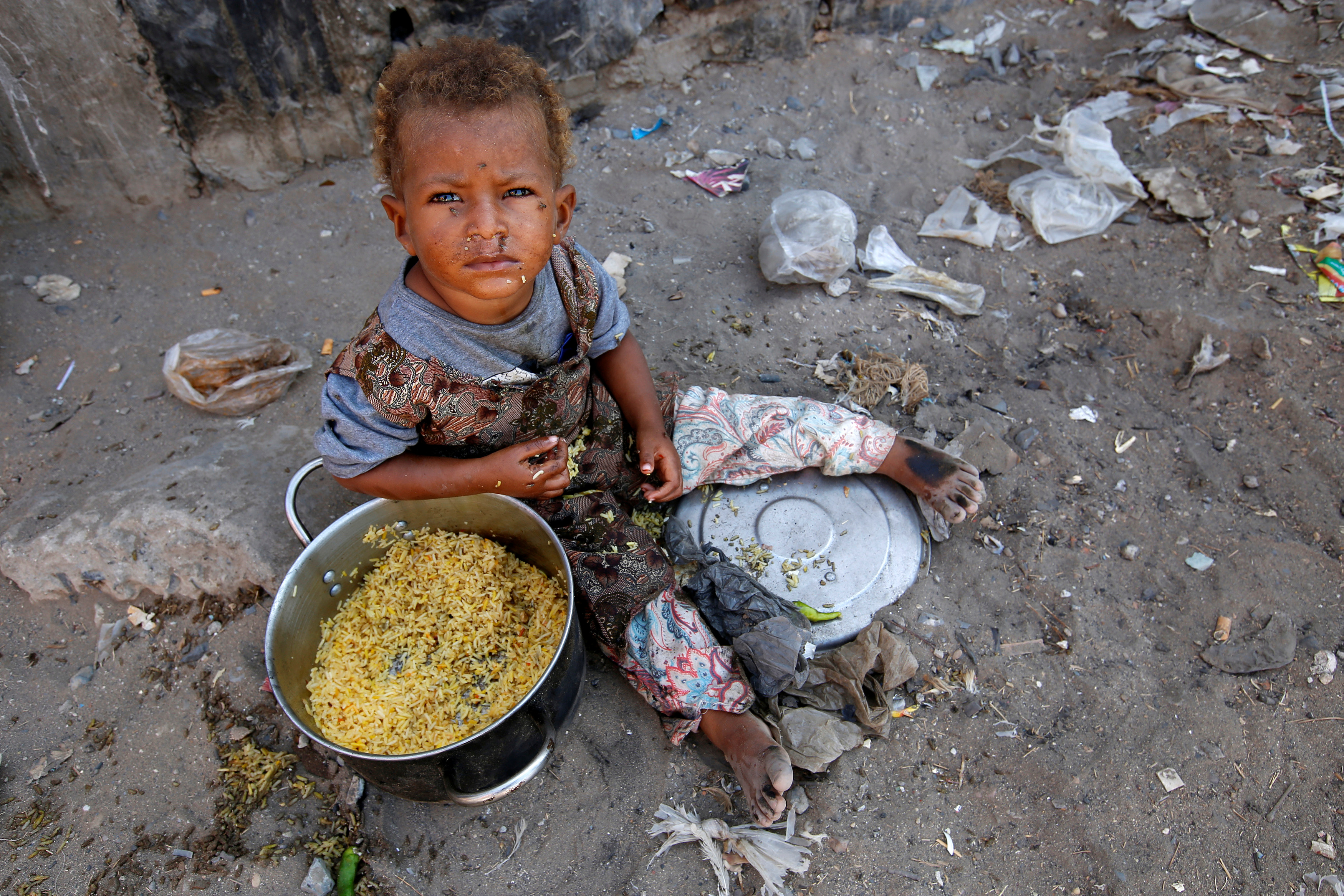 A girl displaced by the war in the northwestern areas of Yemen eats outside her family's makeshift hut on a street in the Red Sea port city of Hodeida, Yemen December 25, 2017.