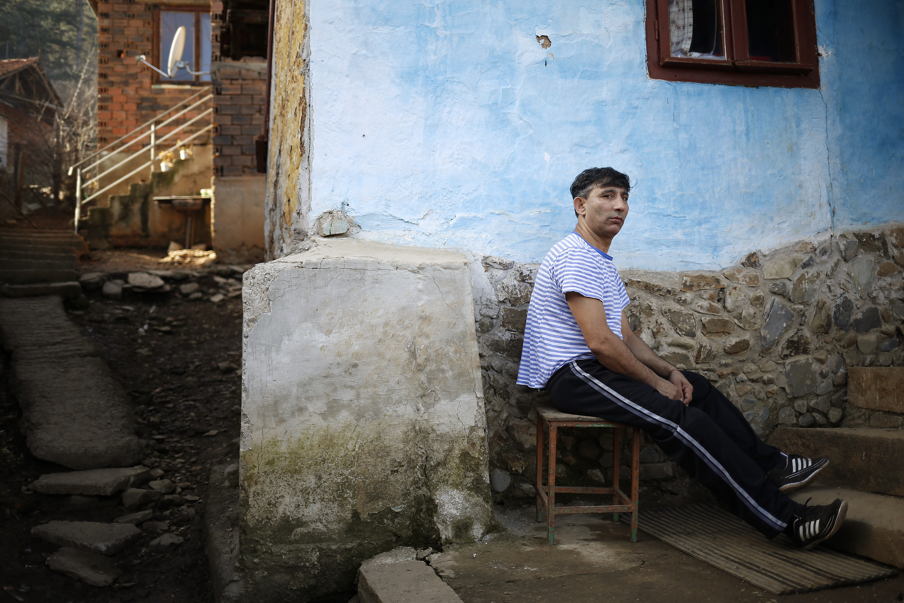 FILE - Bulgarian Roma man Georgi Petrov poses for a picture in front of his house in the village of Vrachesh, Jan. 21, 2015.