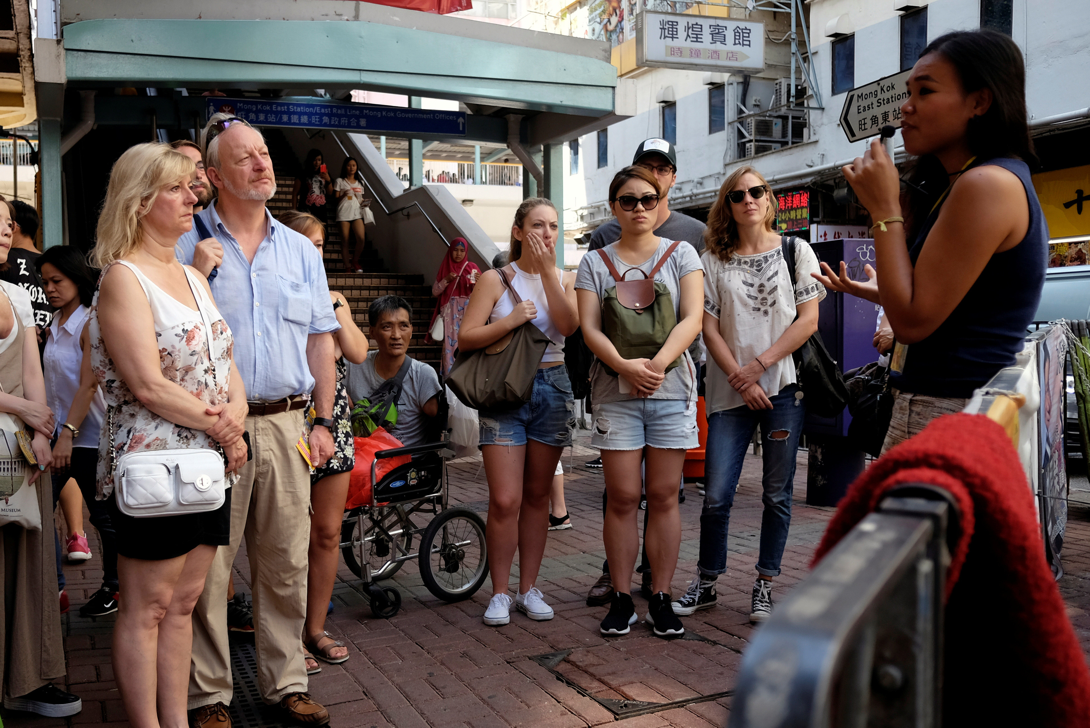 FILE - Tour guide Alla Lau, right, speaks to tourists who join a free tour at Mong Kok district in Hong Kong, China, Aug. 6, 2017.