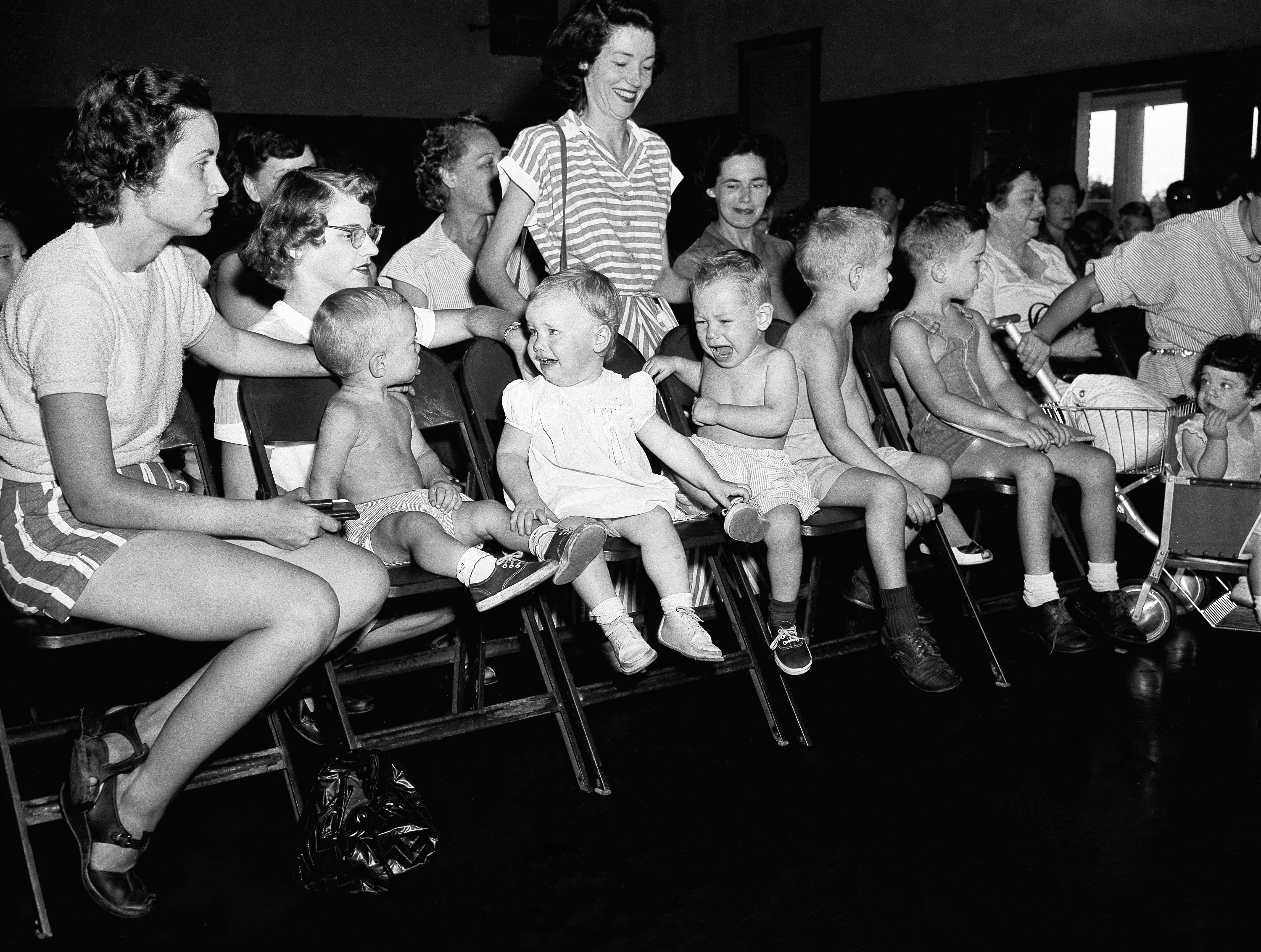 Three toddlers awaiting their turn to be inoculated with gamma globulin, blood fraction, in a mass experiment to prevent paralysis from polio, don't seem to be happy about it, July 2, 1952 in Houston.