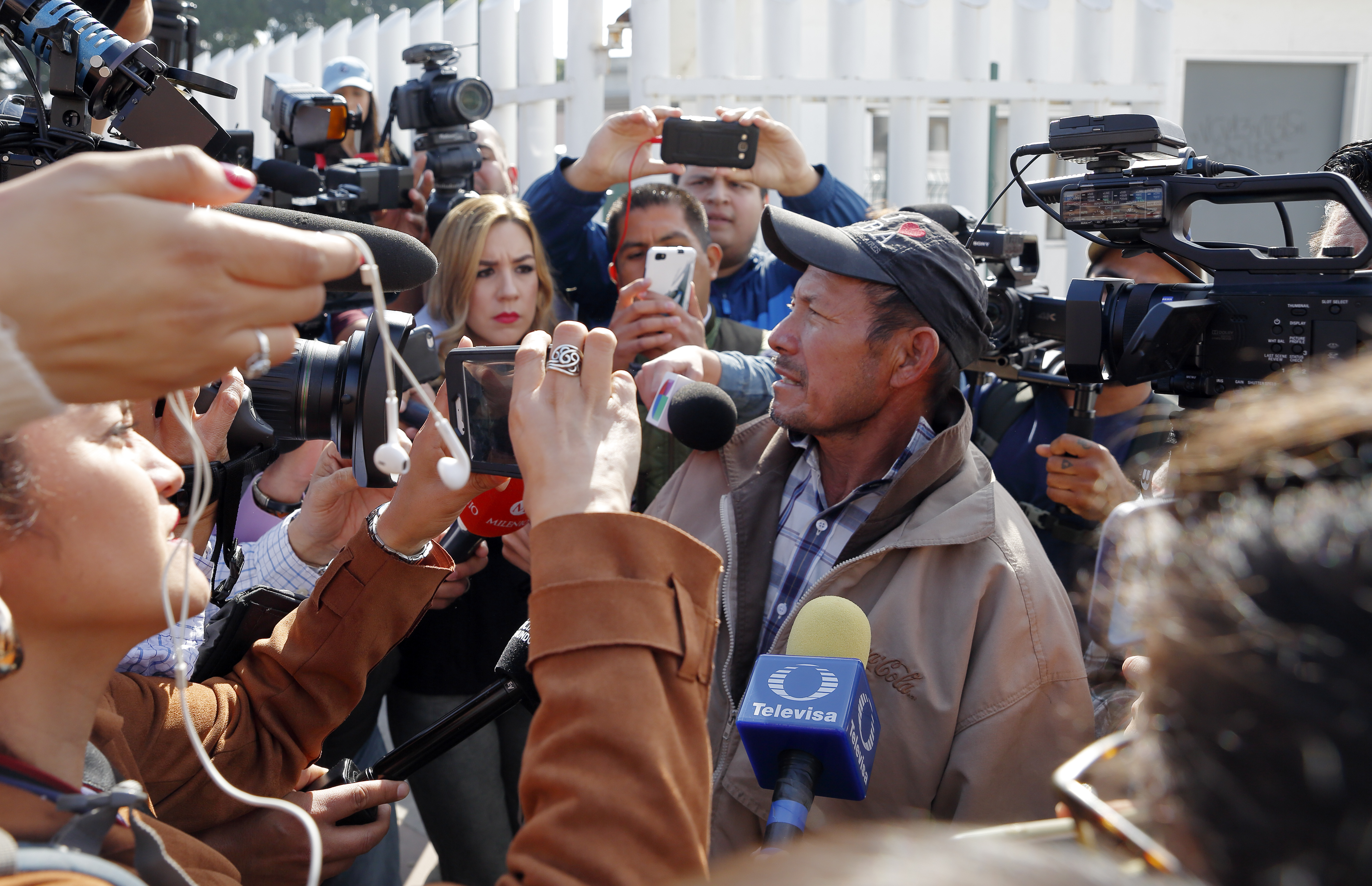 Carlos Catarldo Gomez, of Honduras, right, is surrounded by reporters after leaving the United States, the first person returned to Mexico to wait for his asylum hearing date, in Tijuana, Mexico, Jan. 29, 2019. The Trump administration has launched a...