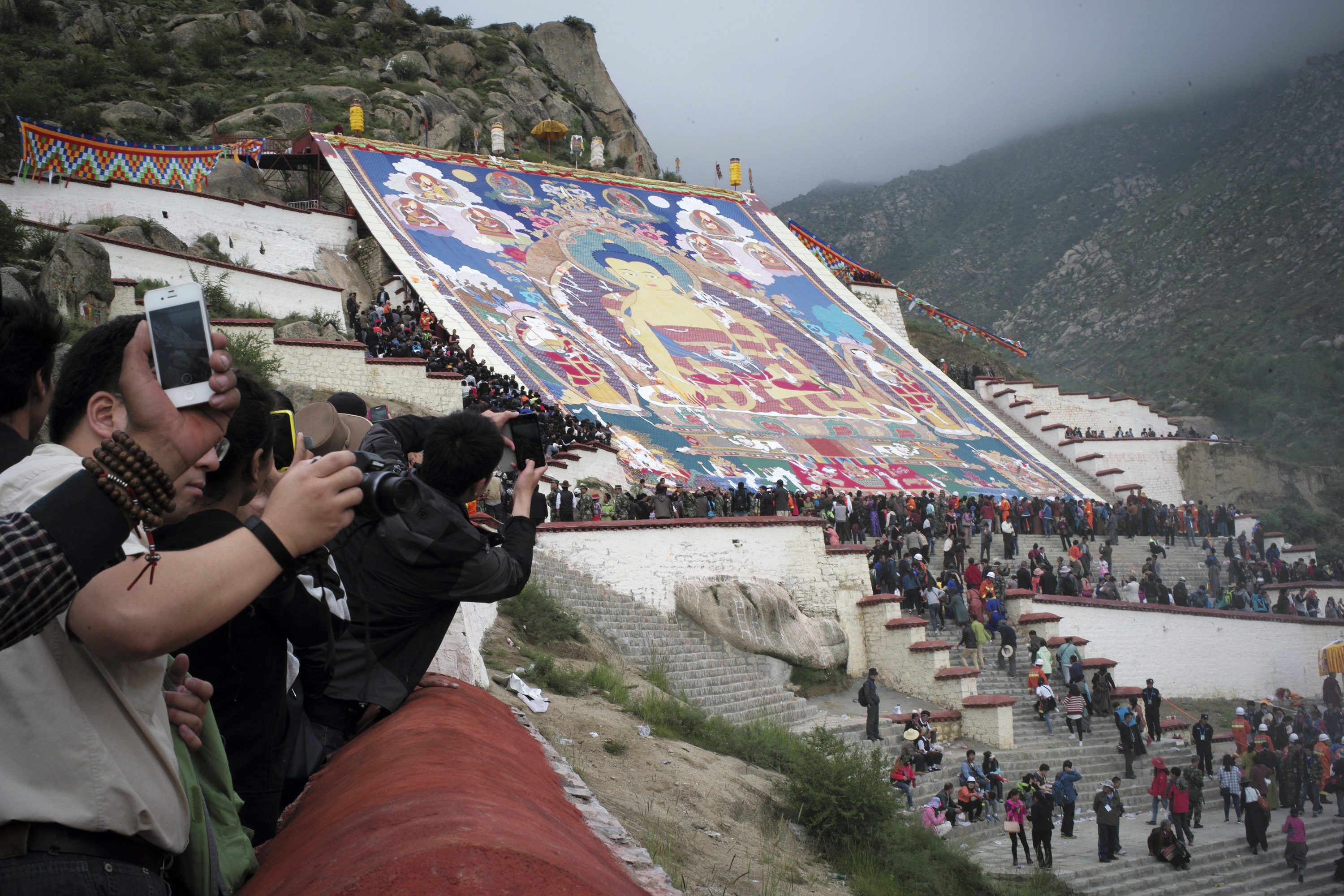 Tibetan Buddhists, tourists view a huge Thangka, a religious silk embroidery or painting displaying a Buddha portrait, during the Shoton Festival at Zhaibung Monastery in Lhasa, capital of southwest China's Tibet Autonomous Region, Aug. 25, 2014.