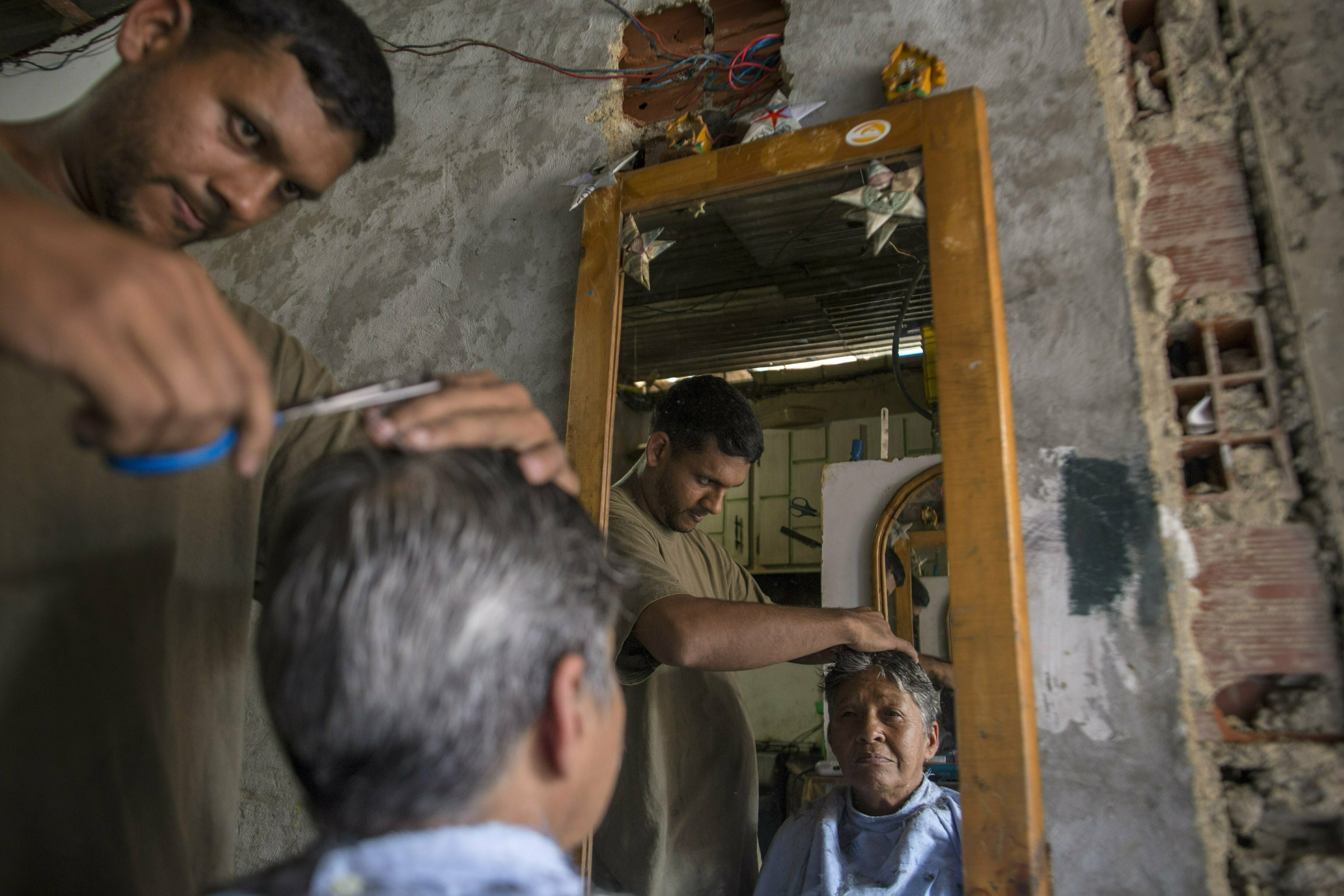Jorge Flores practices his hairstyling skills on his mother Rosa Vega inside his home, where he is trying to set up a barber shop in the Petare slum, in Caracas, Feb. 14, 2019.