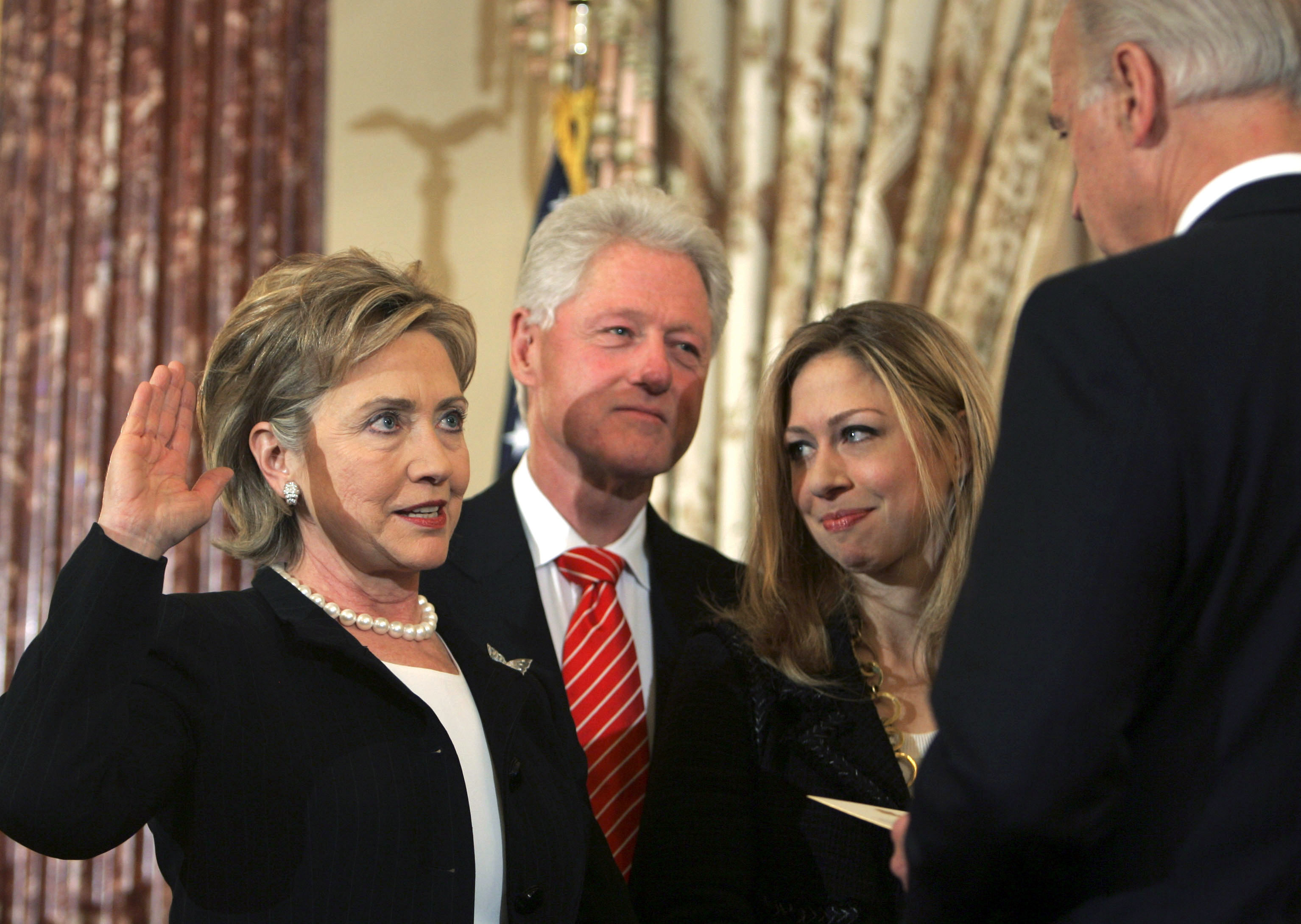Vice President Joe Biden, right, swears in Secretary of State Hillary Clinton in a ceremonial swearing-in at the State Department in Washington, accompanied by her husband, former President Bill Clinton, and their daughter, Chelsea.