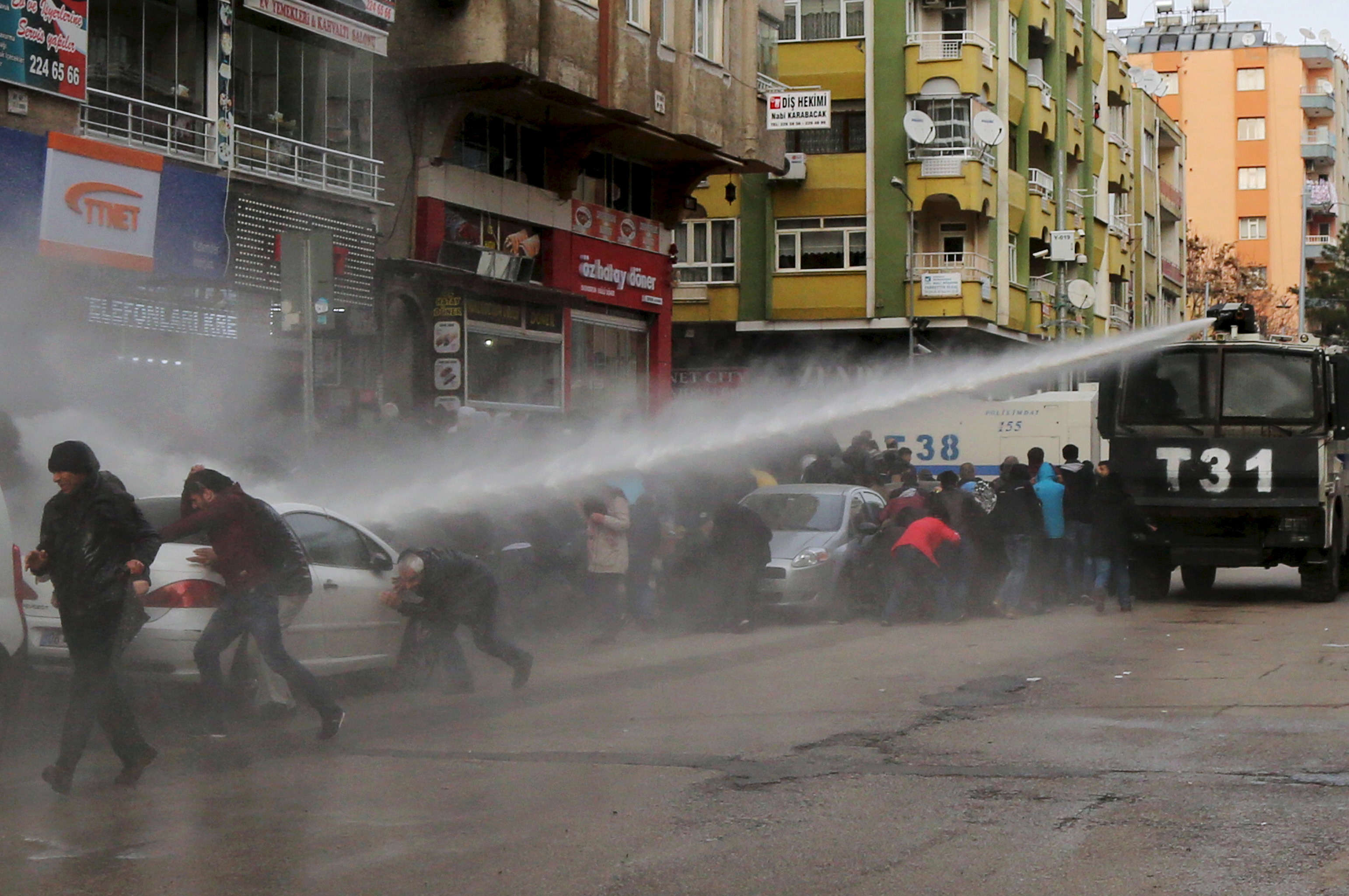 Turkish riot police use a water cannon to disperse Kurdish demonstrators during a protest against a curfew in Sur district and security operations in the region, in the southeastern city of Diyarbakir, Turkey January 17, 2016.