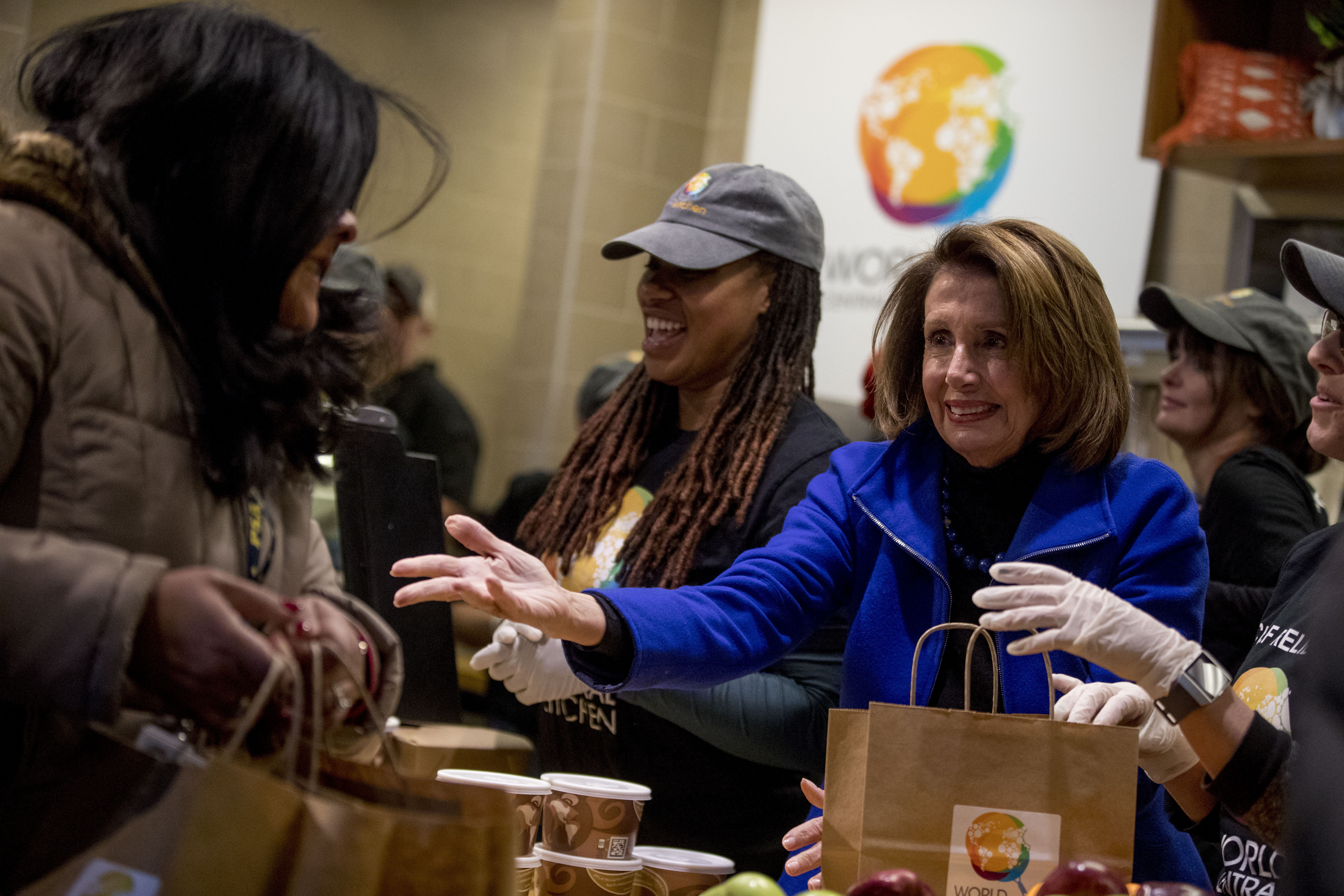 House Speaker Nancy Pelosi of California, center, helps give out food at World Central Kitchen, the not-for-profit organization started by Chef Jose Andres  Jan. 22, 2019, in Washington.
