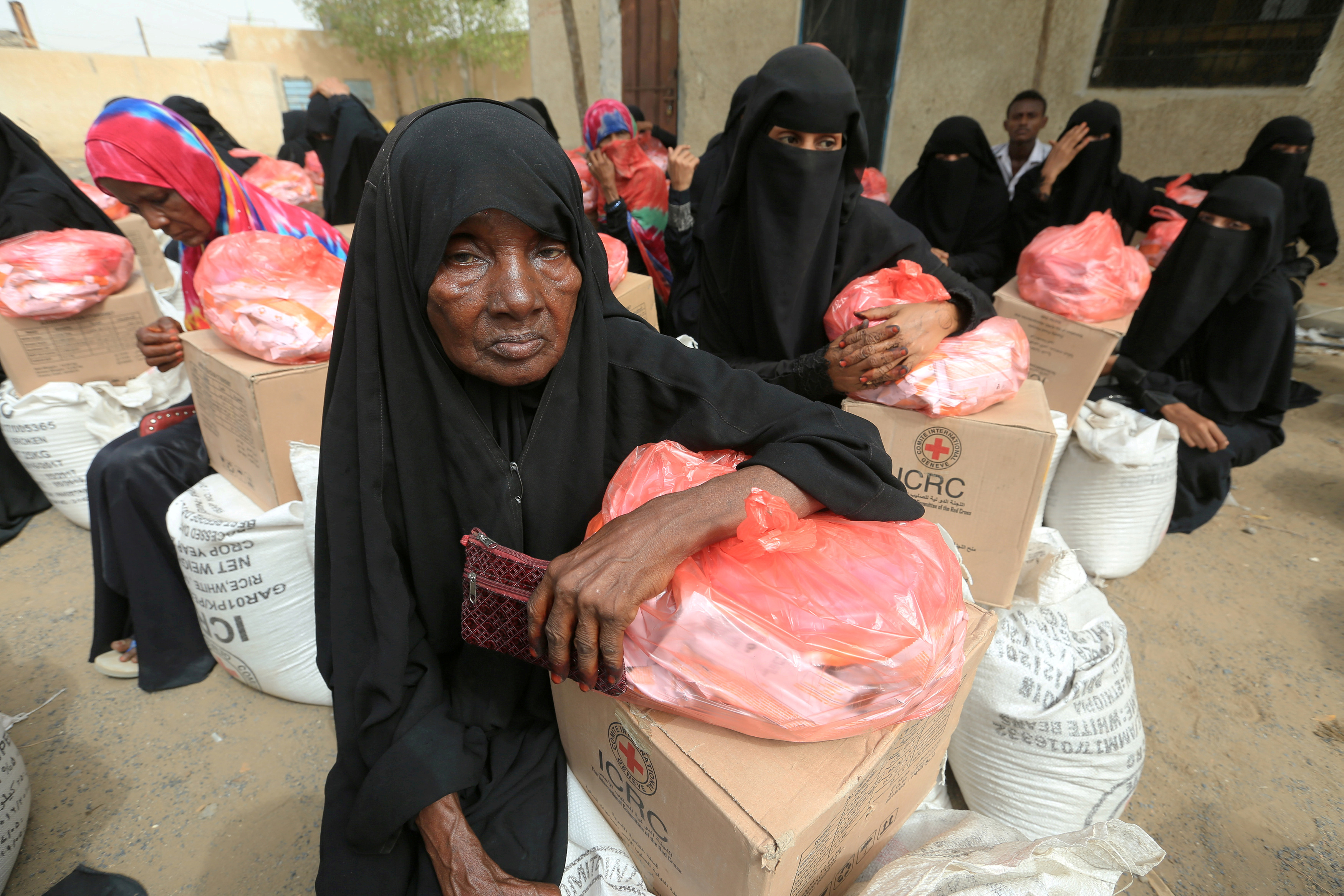 Women sit next to food aid delivered by the International Committee of the Red Cross to internally displaced people in the Red Sea port city of Hodeida, Yemen, July 21, 2018.
