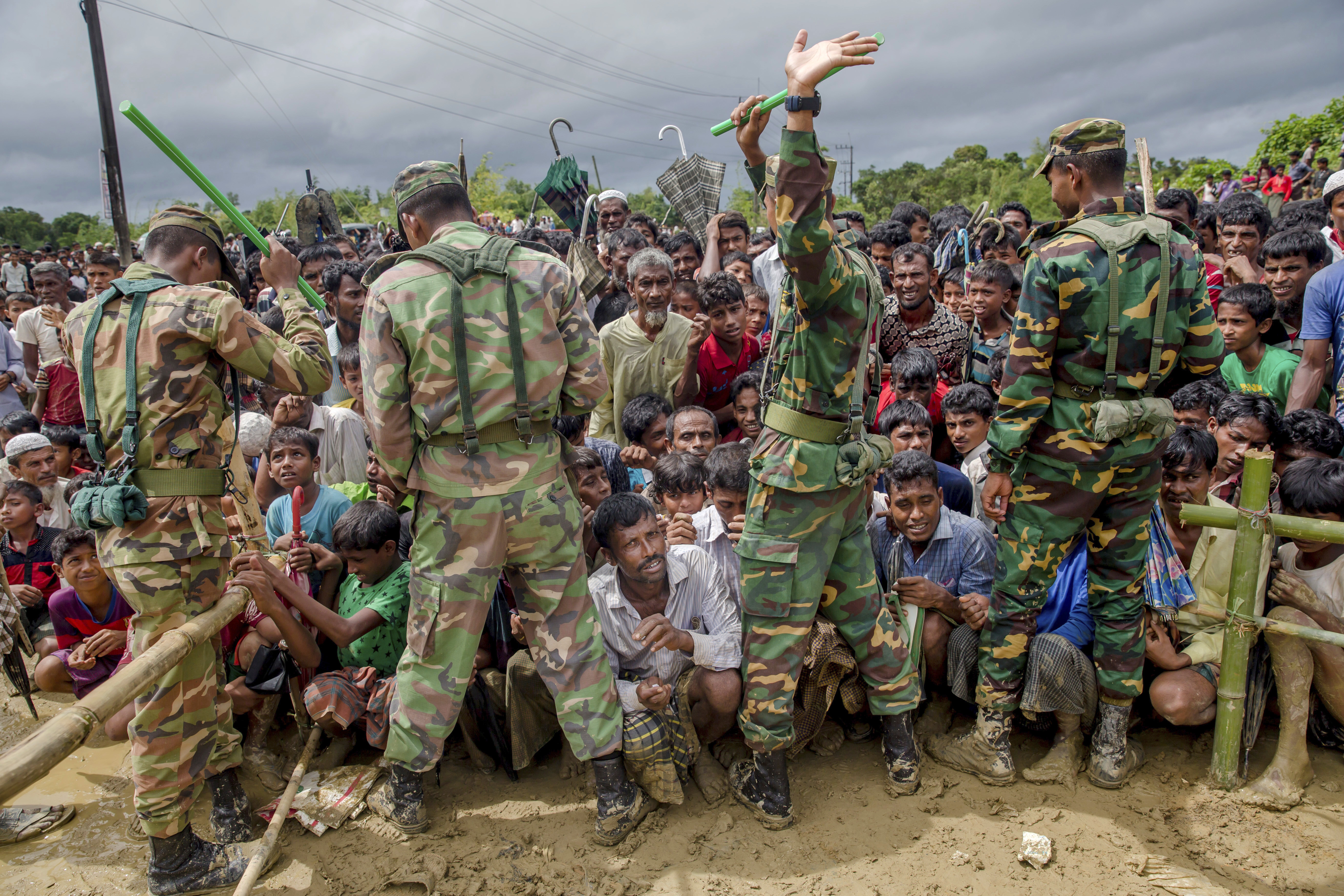 Bangladesh soldiers stand guard as Rohingya Muslims, who crossed over from Myanmar into Bangladesh, wait to receive aid from a refugee camp near Balukhali, Sept. 28, 2017.
