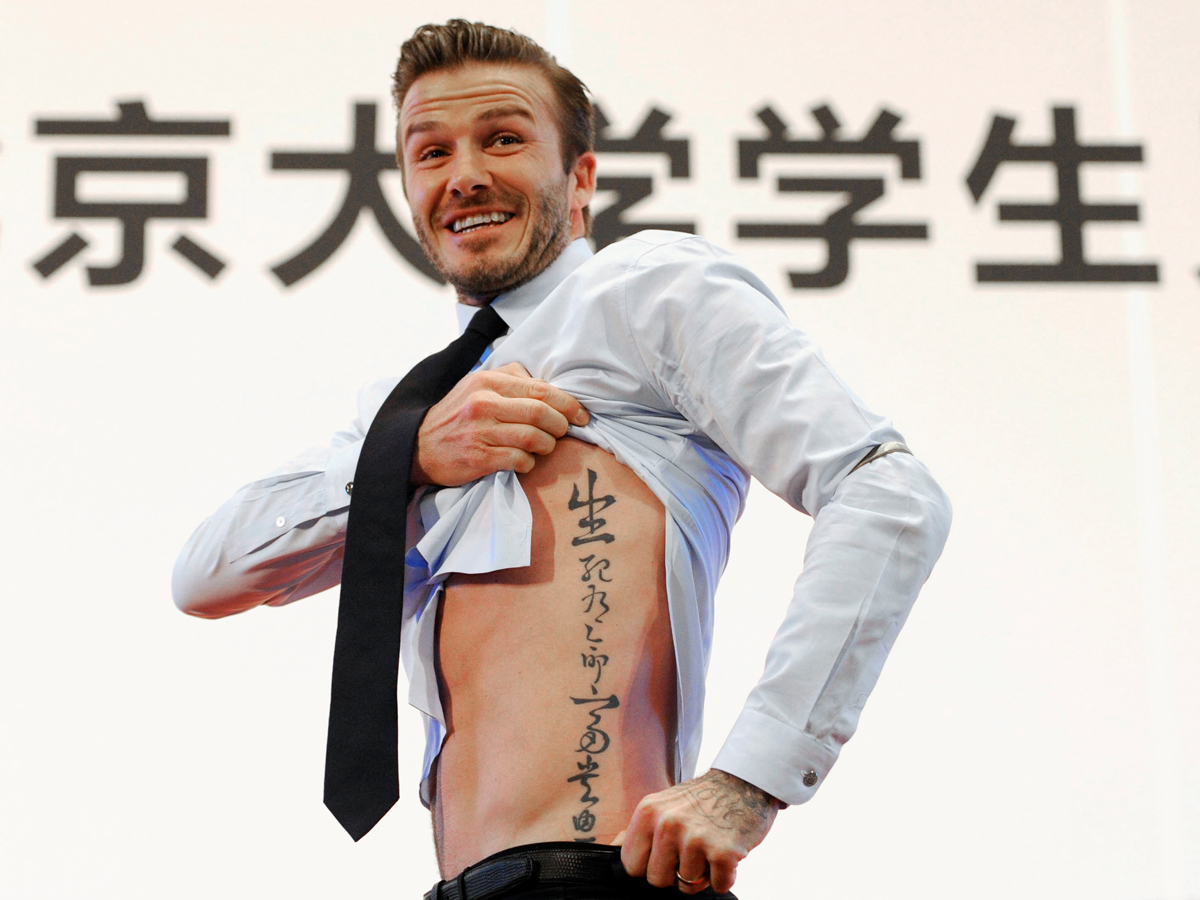 """Beckham shows his tattoo after he was asked to by students at Peking University during his visit to Beijing March 24, 2013. The tattoo in Chinese characters reads, """"Life and death are determined by fate, rank and riches decreed by Heaven."""""""