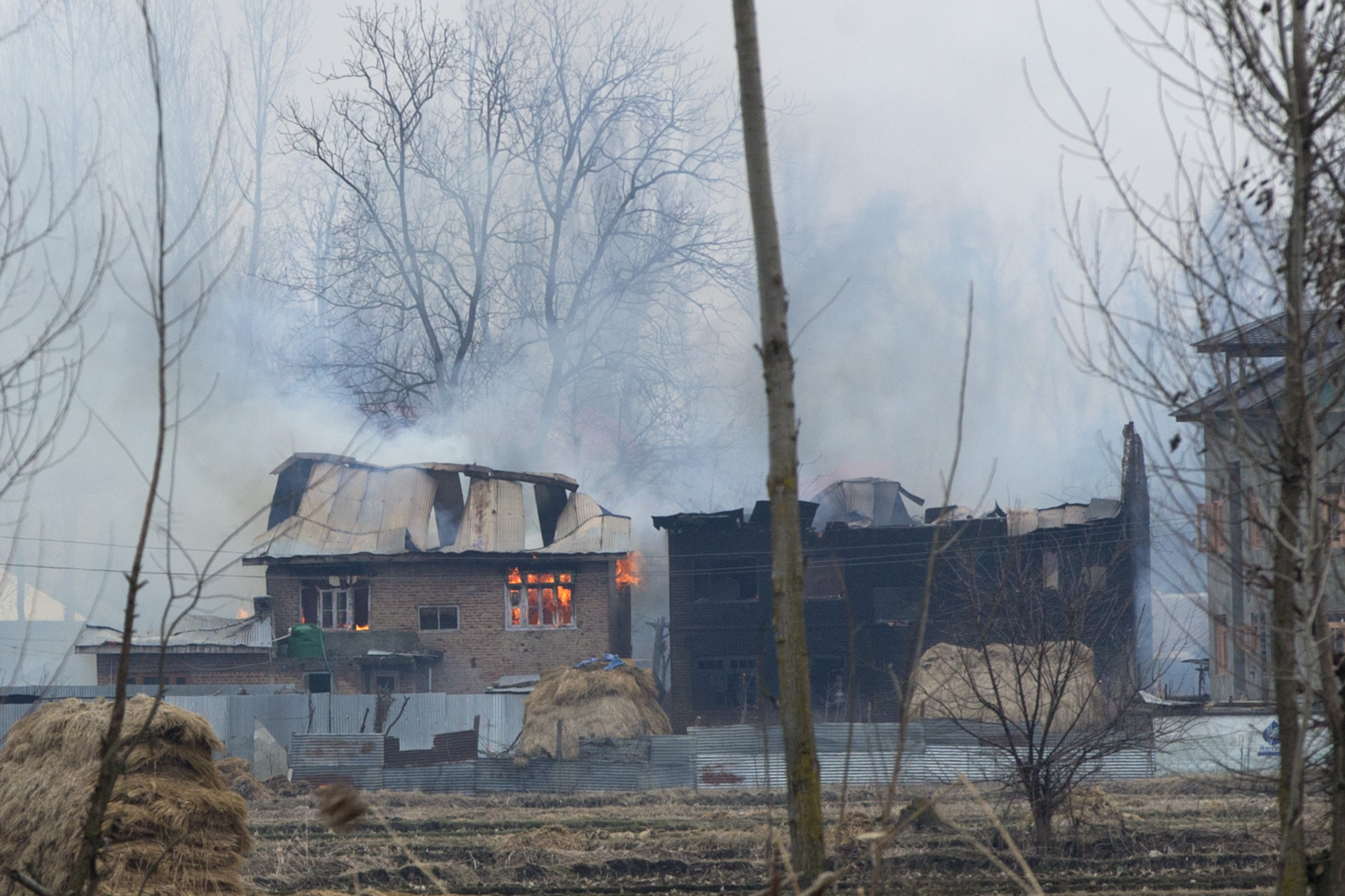 Flames and smoke billows from residential buildings where militants are suspected to have taken refuge during a gun battle in Pulwama, south of Srinagar, Indian controlled Kashmir, Feb. 18, 2019.
