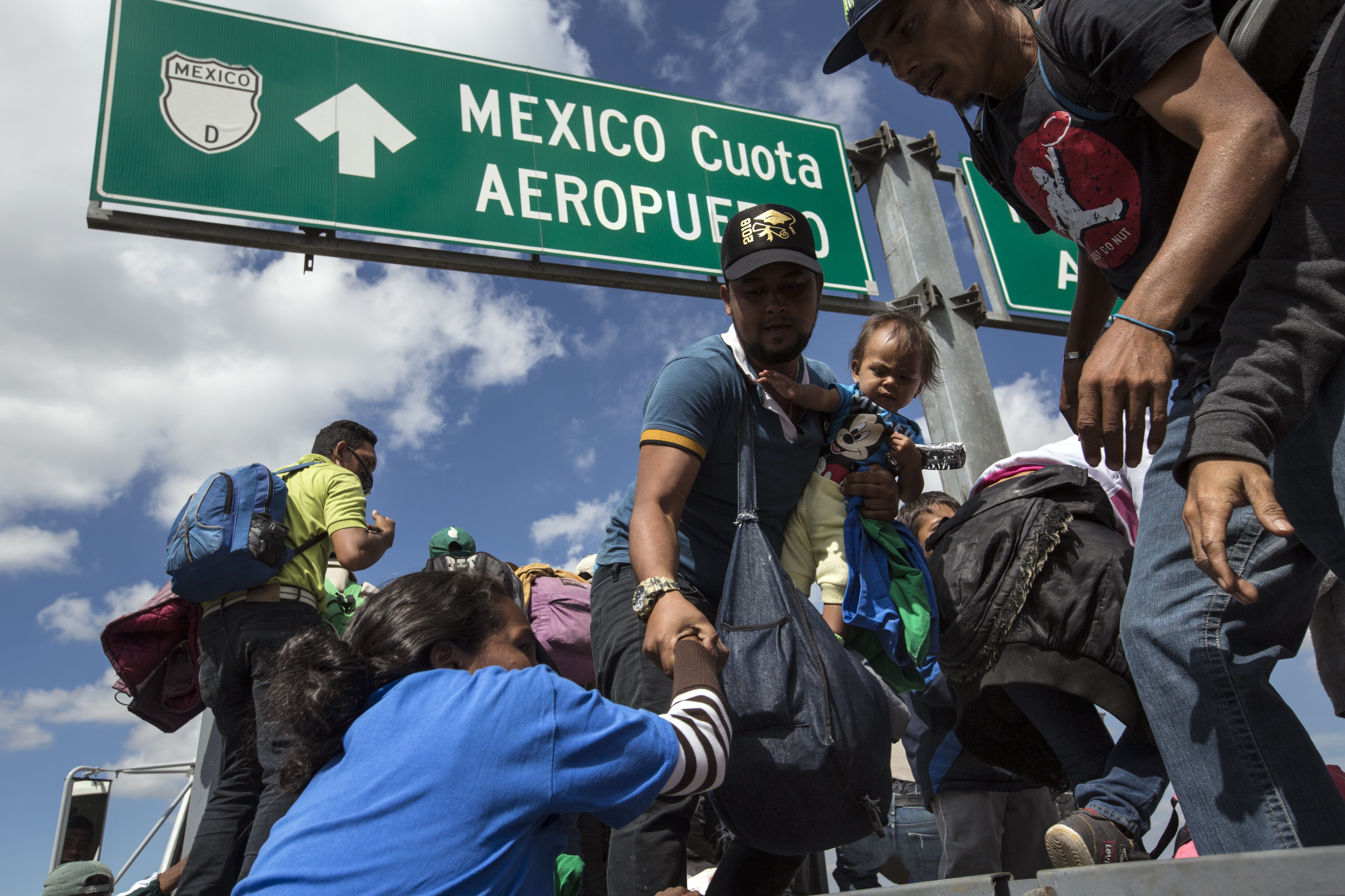 U.S.-bound Central American migrants get on to a truck for a a free ride, as part of a thousands-strong caravan moving through Puebla, Mexico, Monday, Nov. 5, 2018.