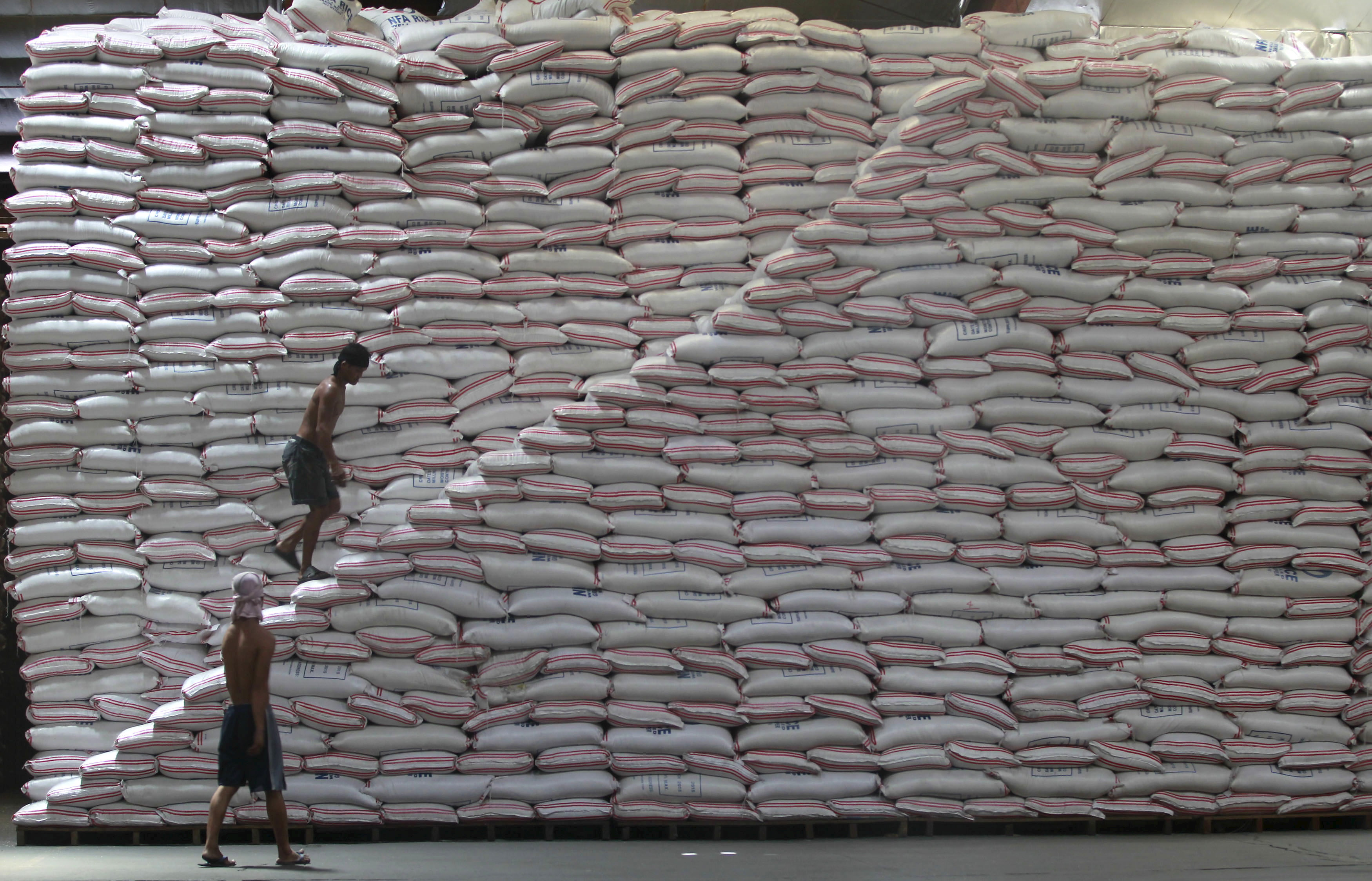 A worker walks up a pile of rice at a warehouse of the Philippines National Food Authority in Manila, May 12, 2015.