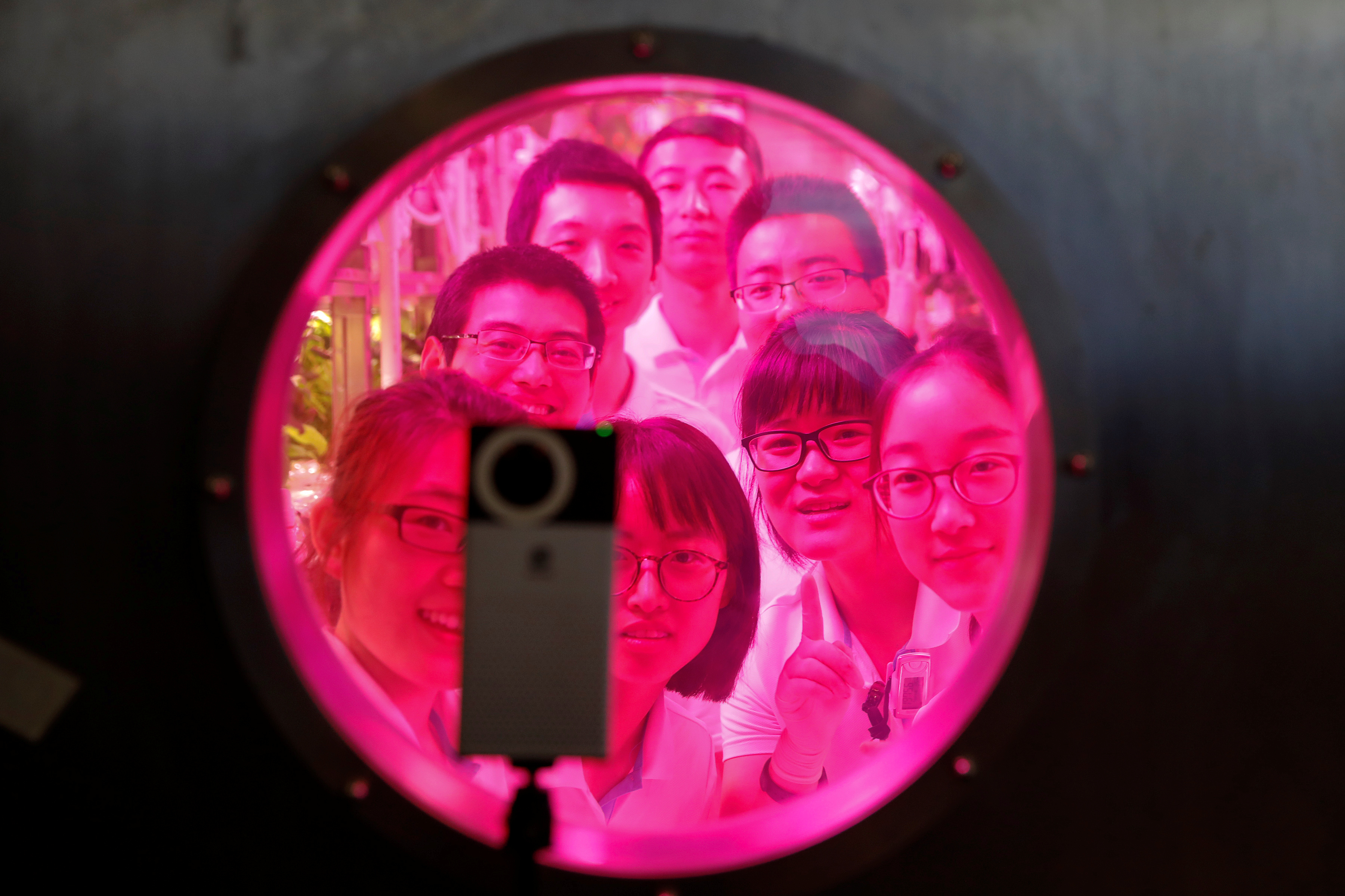 Volunteers smile to a camera from inside a simulated space cabin in which they temporarily live as a part of a scientistic Lunar Palace 365 Project, at Beihang University in Beijing, China, July 9, 2017.