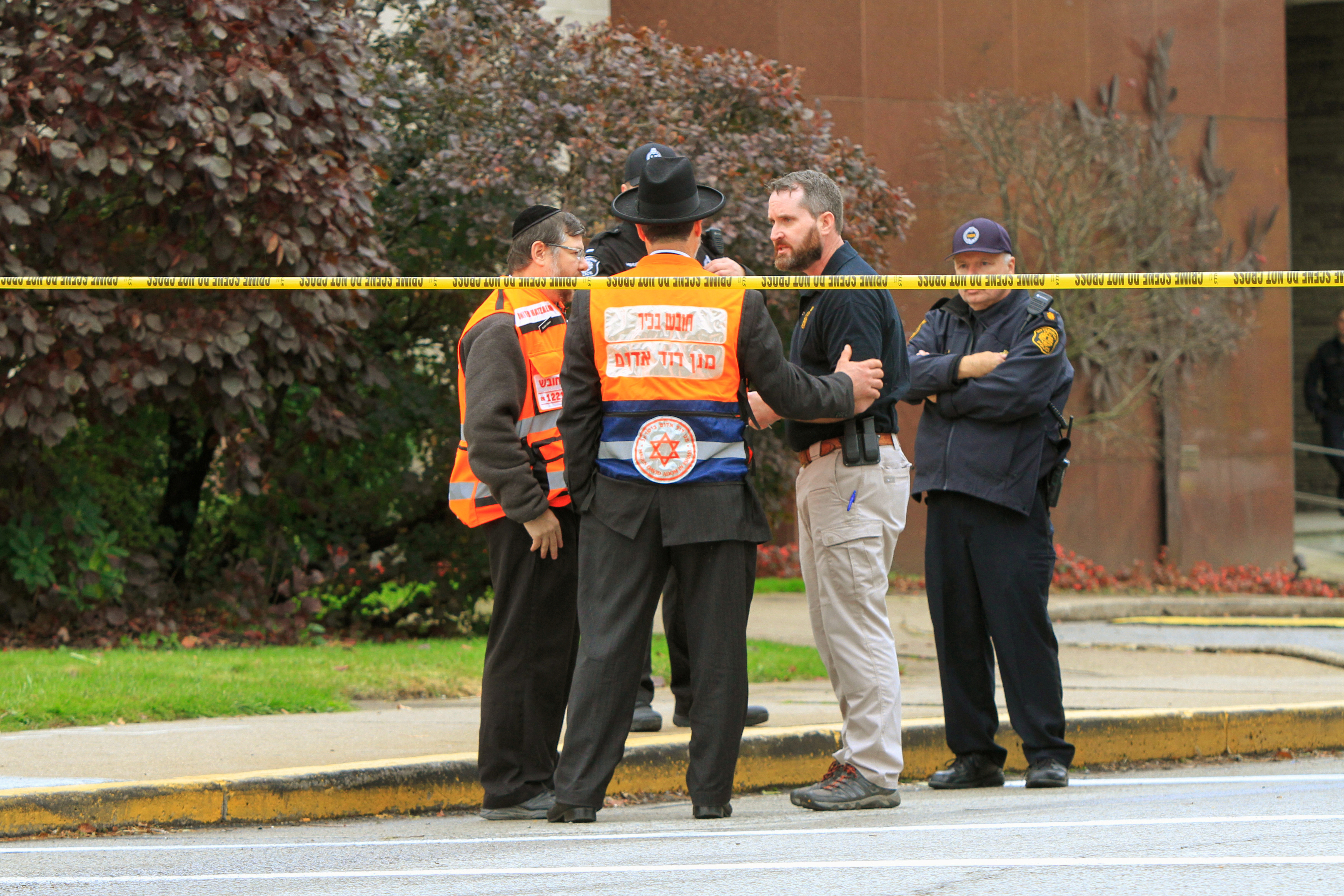 Police officers guarding the Tree of Life Synagogue following a shooting there speak with men in orange vests from a Jewish burial society in Pittsburgh, Pa., Oct. 27, 2018.