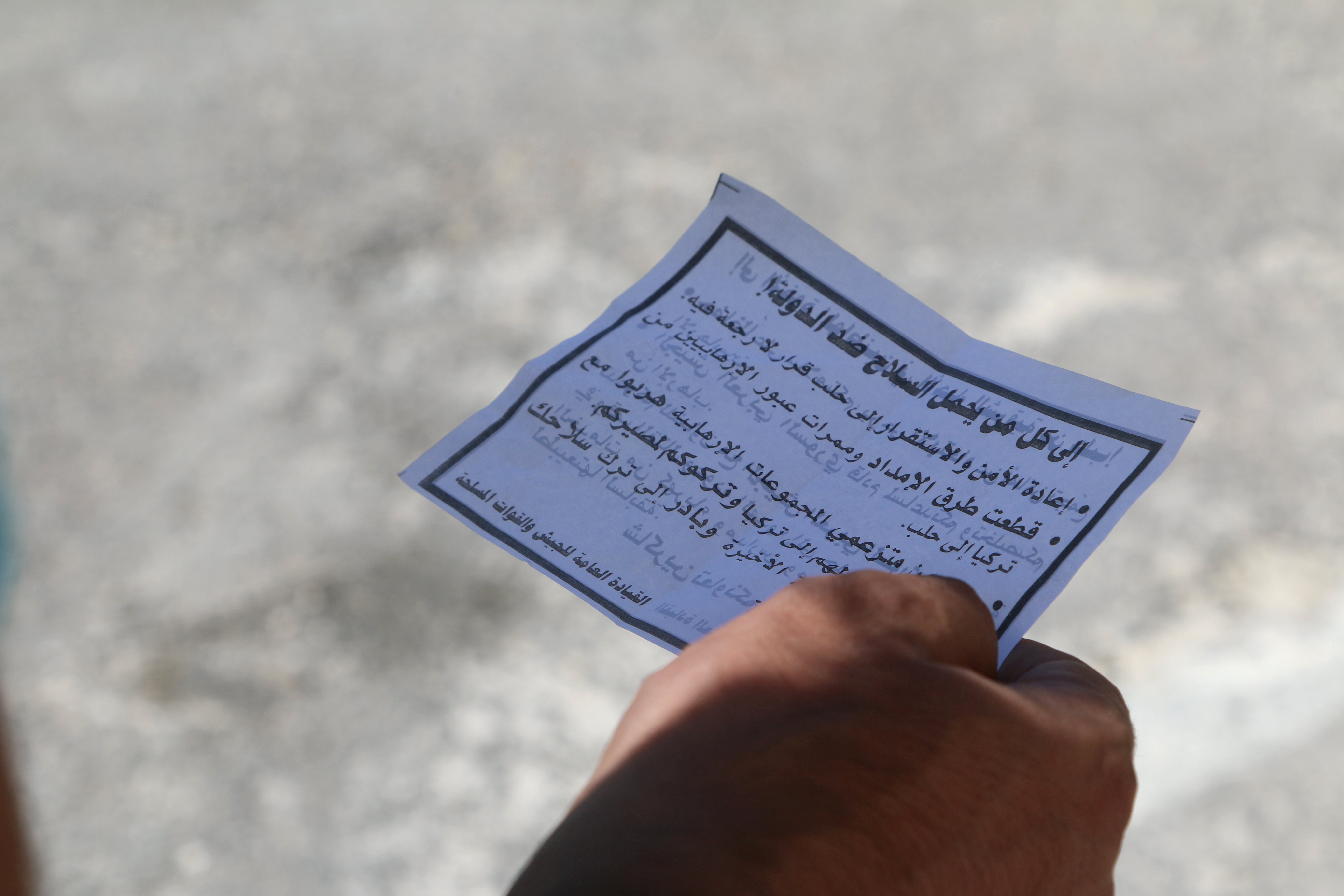 A man holds one of the leaflets dropped by the Syrian army over opposition-held Aleppo districts asking residents to cooperate with the military and calling on fighters to surrender, July 28, 2016.
