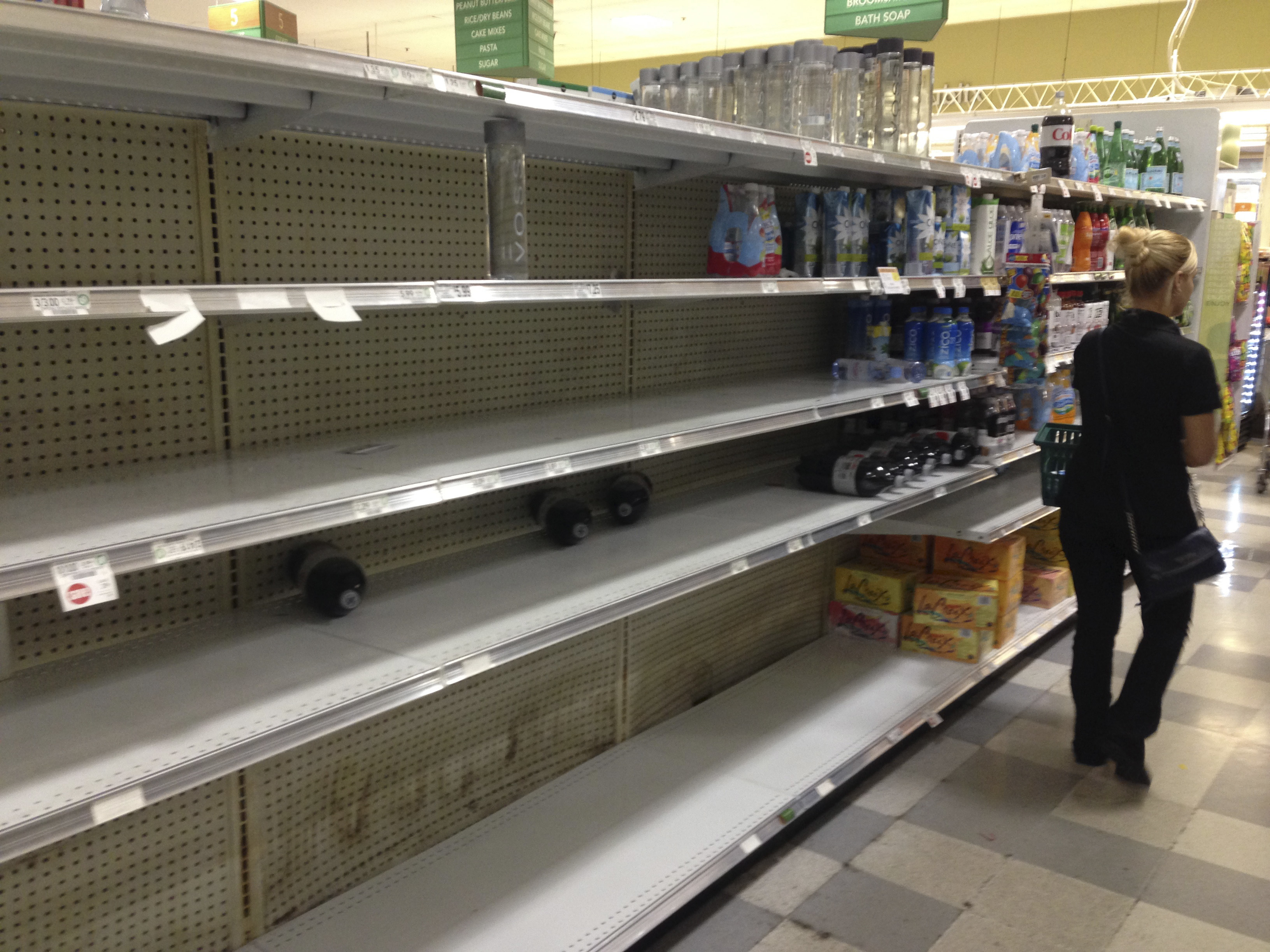 A shopper walks by the empty shelves where bottled water normally would be, at a grocery store in Hollywood, Fla., Oct. 5, 2016.