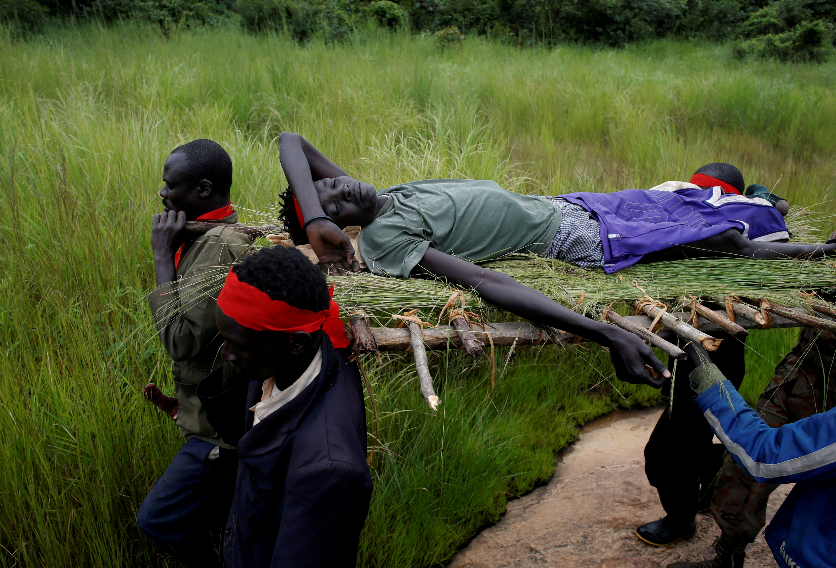 SPLA-IO rebels carry an injured rebel after an assault on government SPLA soldiers, on the road between Kaya and Yondu, South Sudan, Aug. 26, 2017.